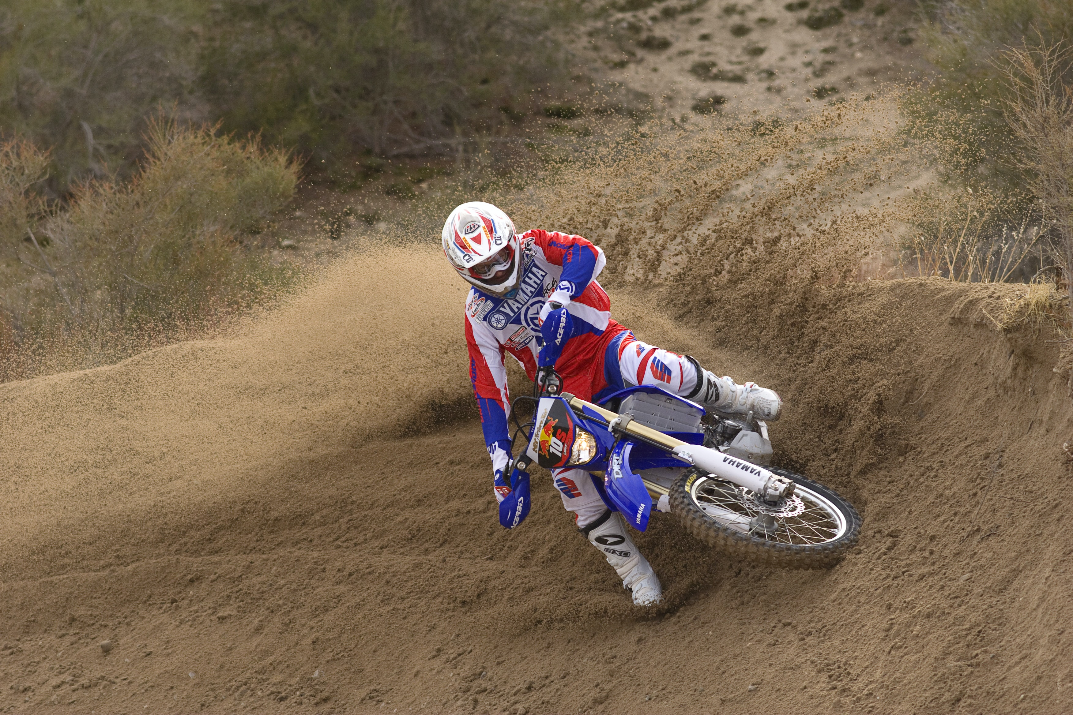 A man turning fast on a dirt hill while riding a dirtbike in Gorman