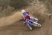 racer riding motocross dirt bike running on brown dirt