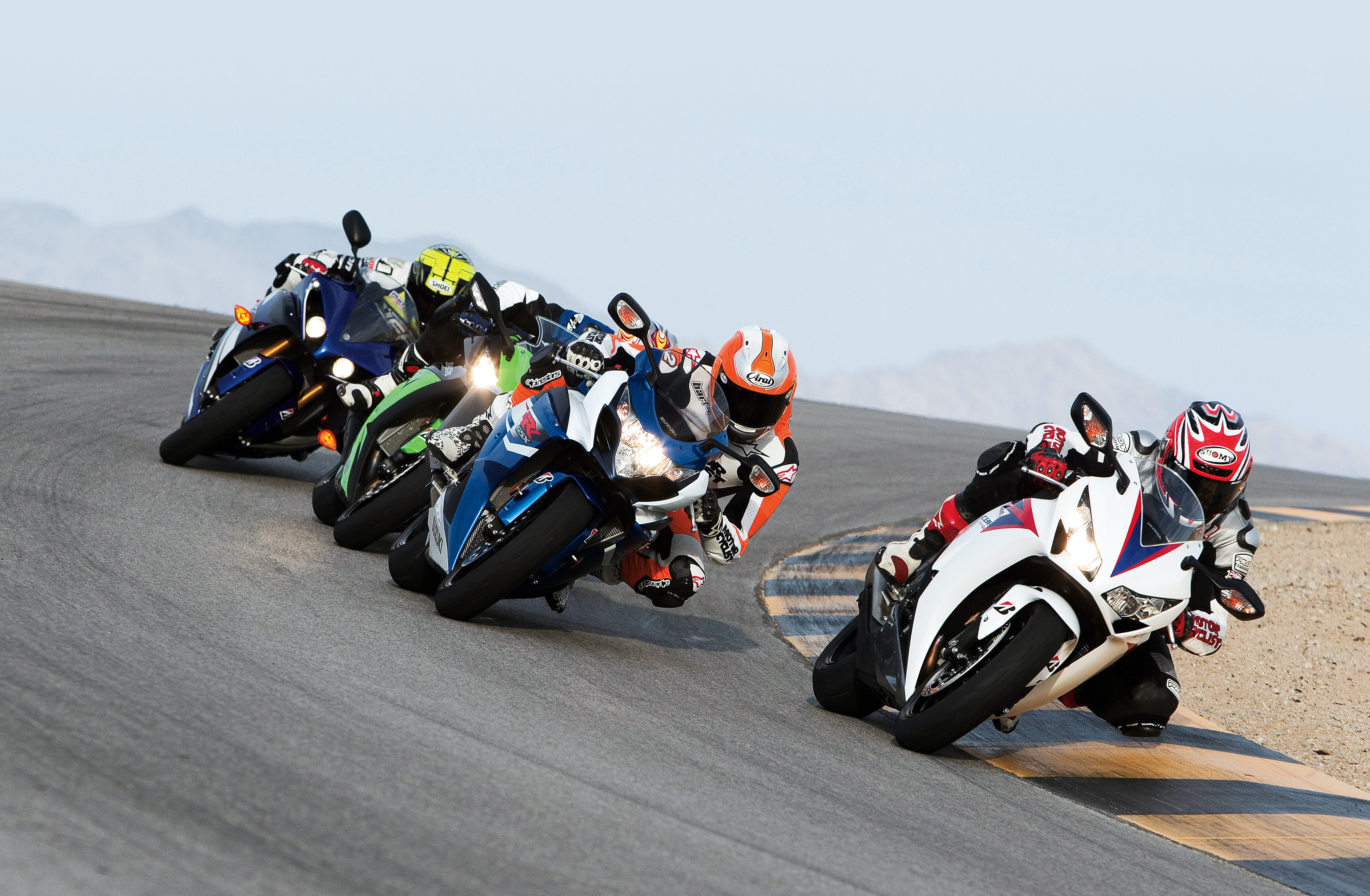 Motorcycle racers drive around a curve during a competition