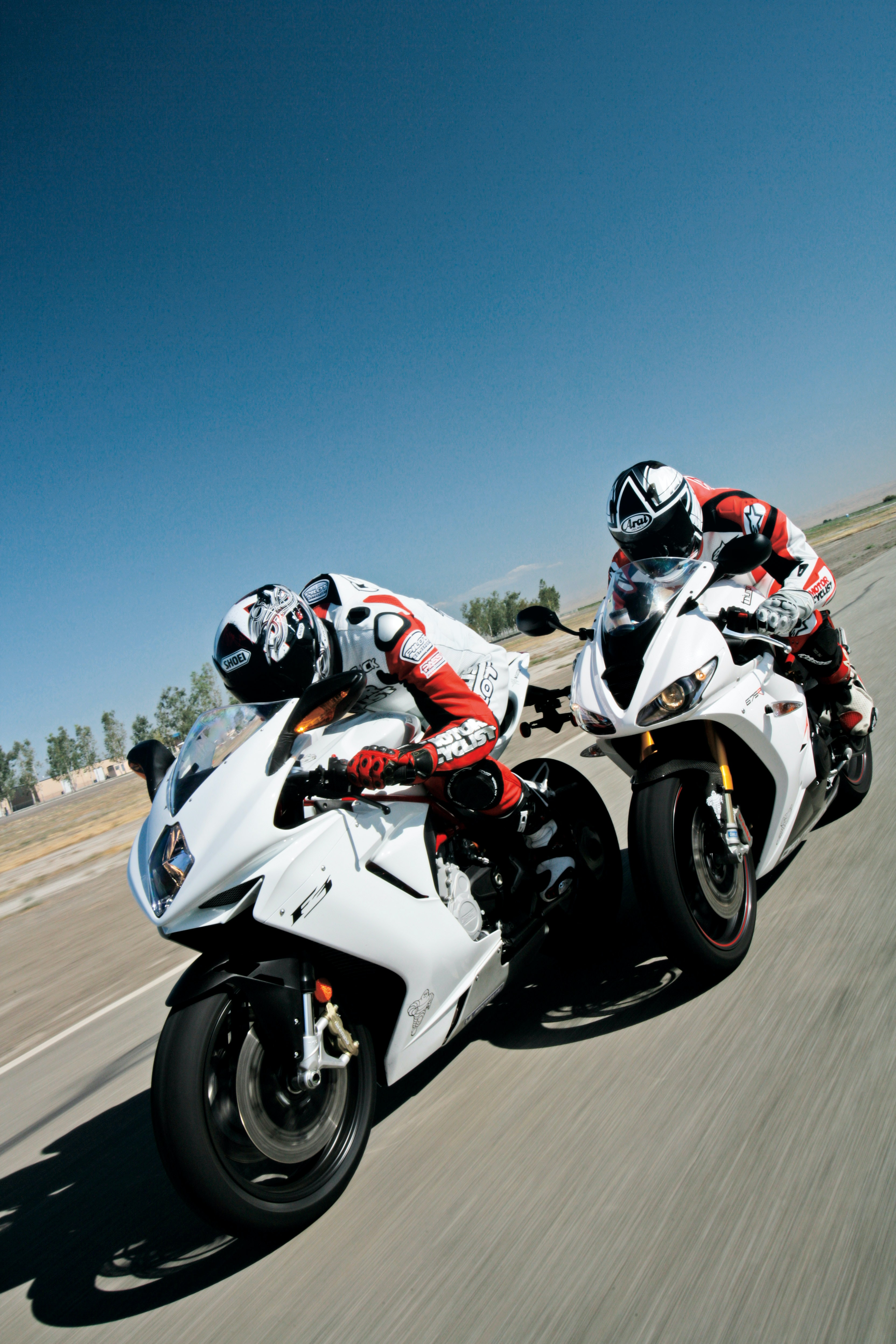 Two people in crash helmets on white motorcycles racing on a track under a blue sky