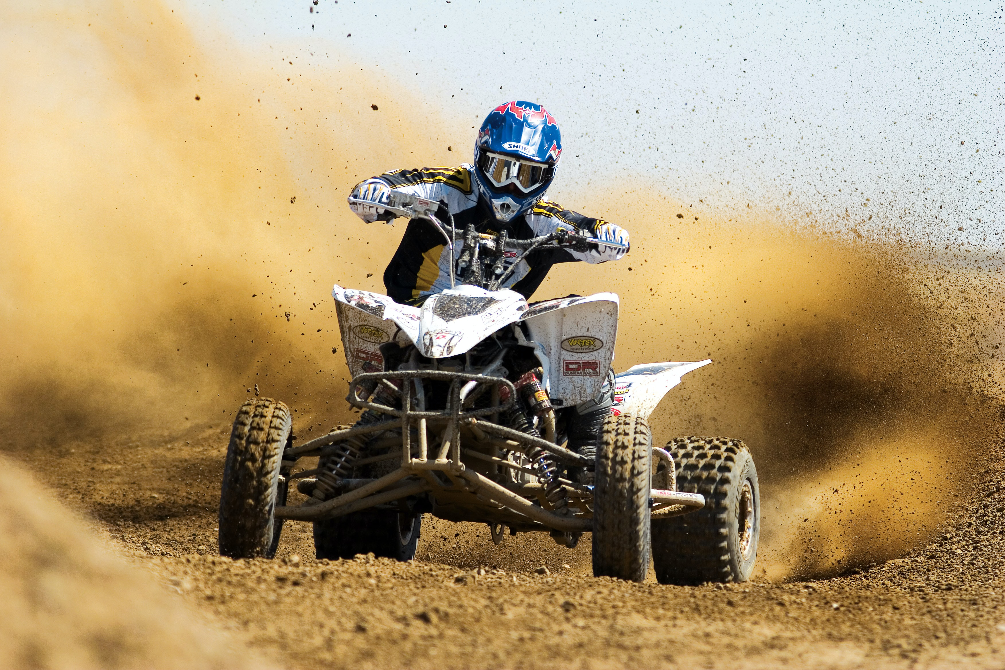 An off road quad racer driving through the dirt on a motorsport race track