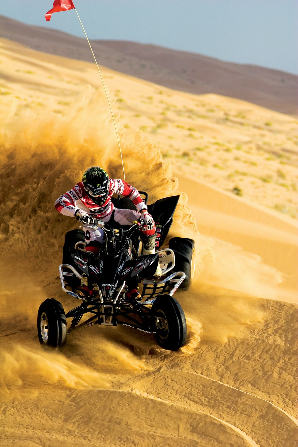 person riding on ATV and drift on sand