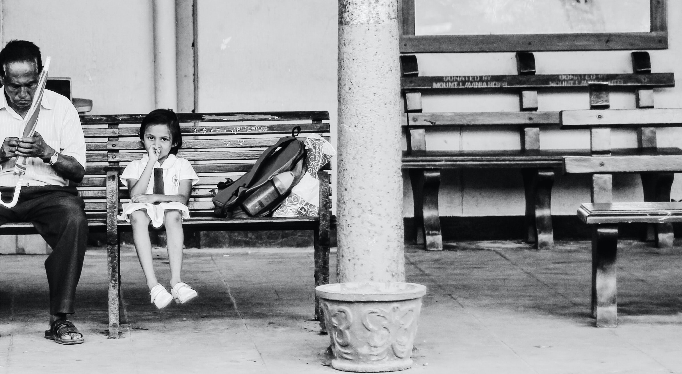 A black and white photo of a man holding an umbrella sitting on a bench at a platform with his daughter