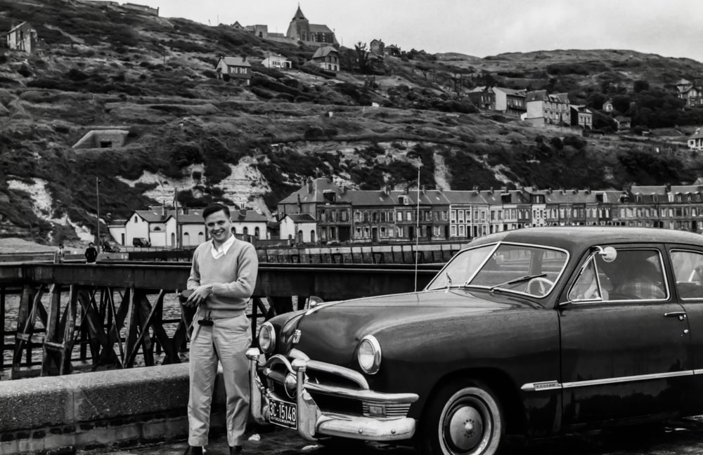 grayscale photography of man standing front of vehicle