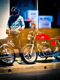 person wearing helmet standing near motorcycle