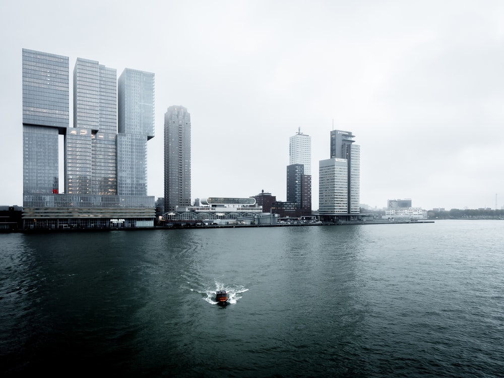 boat in the water with high-rise building in the background