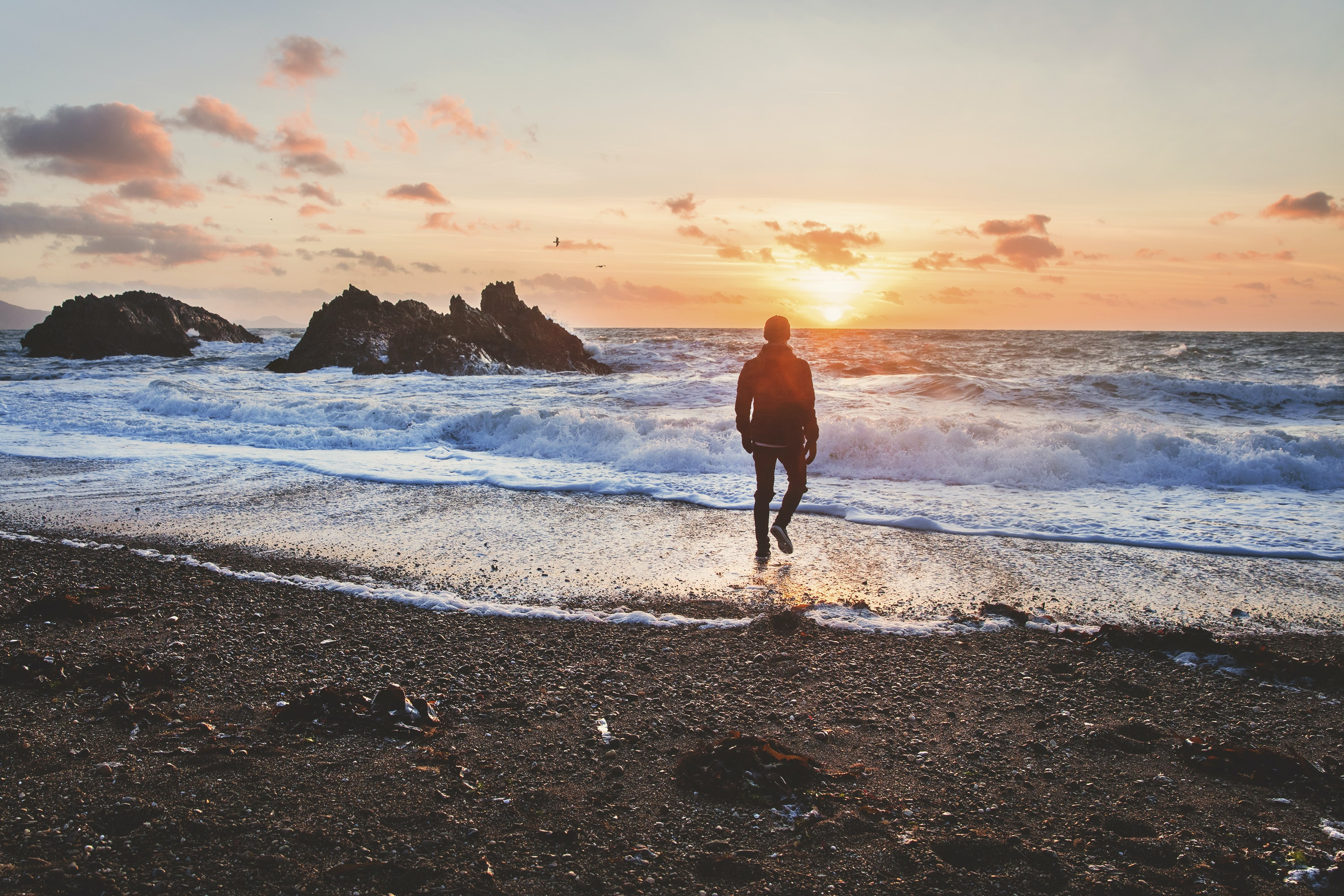 Man walking from beach shoreline to the ocean in Wales during sunset