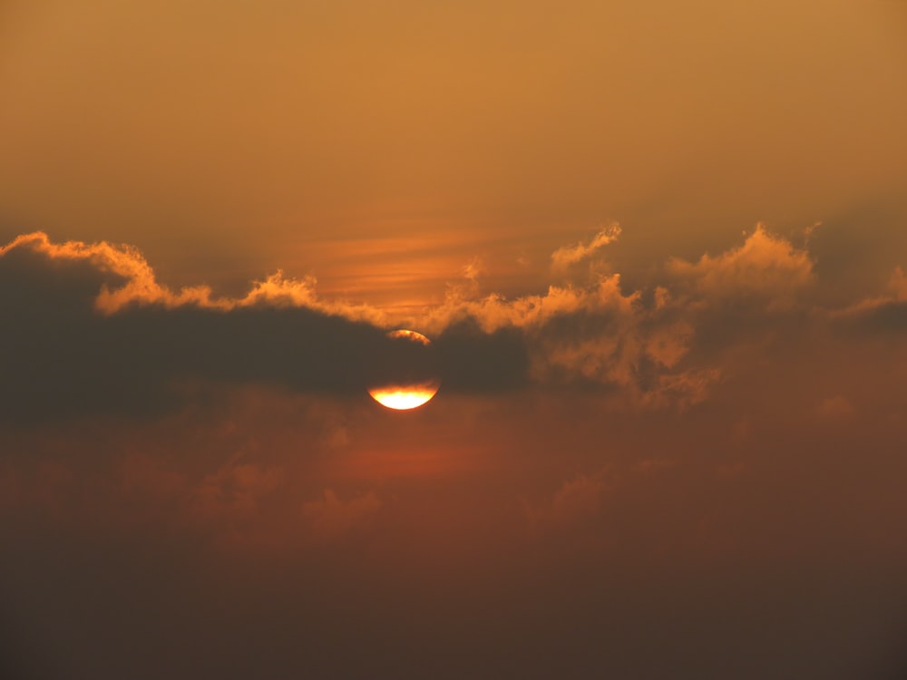 sun covered by clouds at sunset