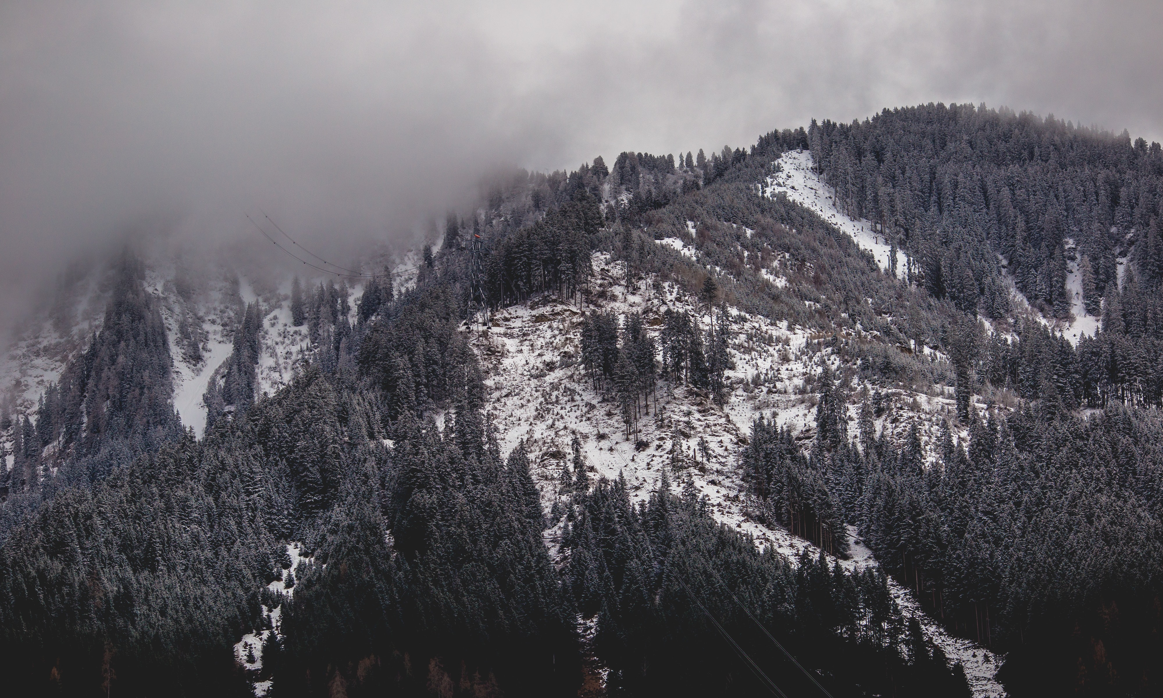 grayscale photography of snowy mountain covered by clouds