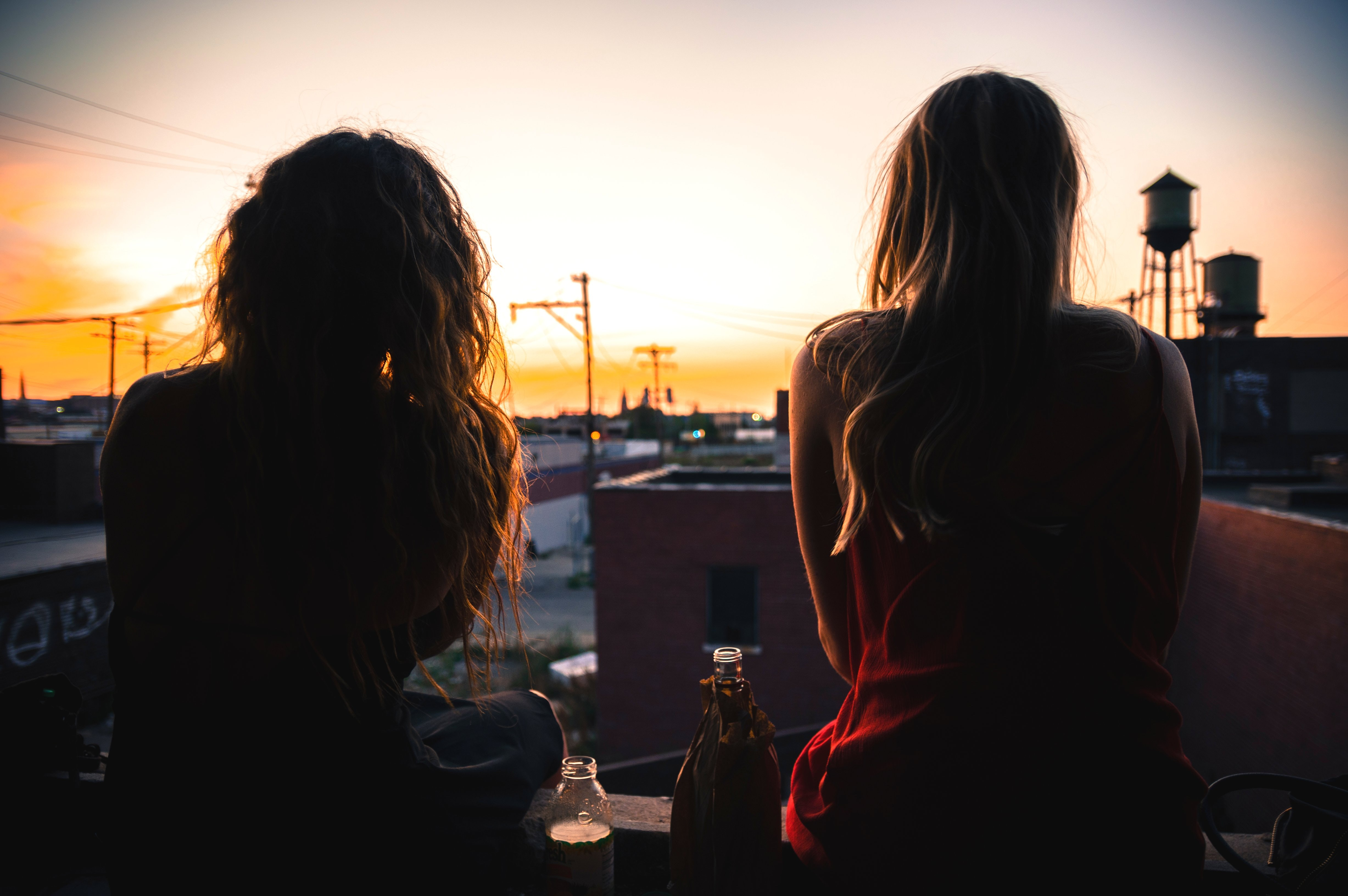 Silhouettes of two women sitting on a rooftop watching the sunset