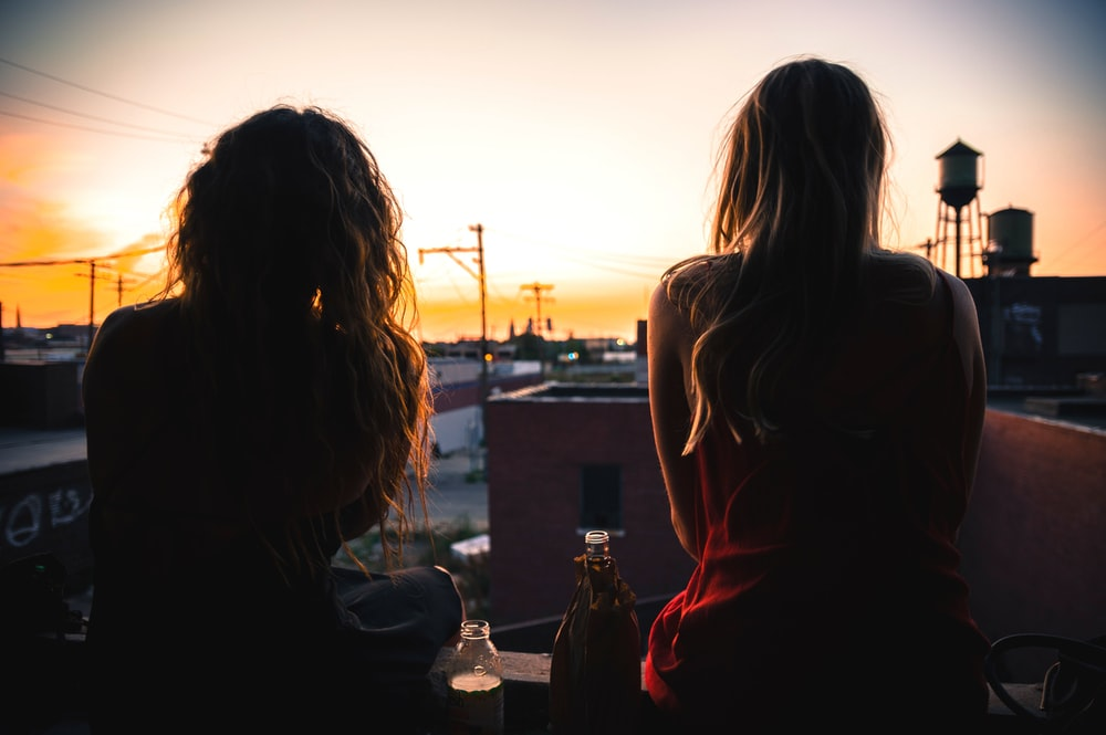 two women sitting on rooftop while watching sunset