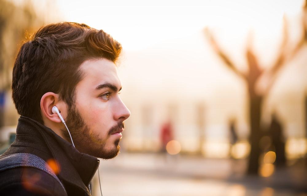 インイヤーイヤホンを聞いている男性のボケライト写真