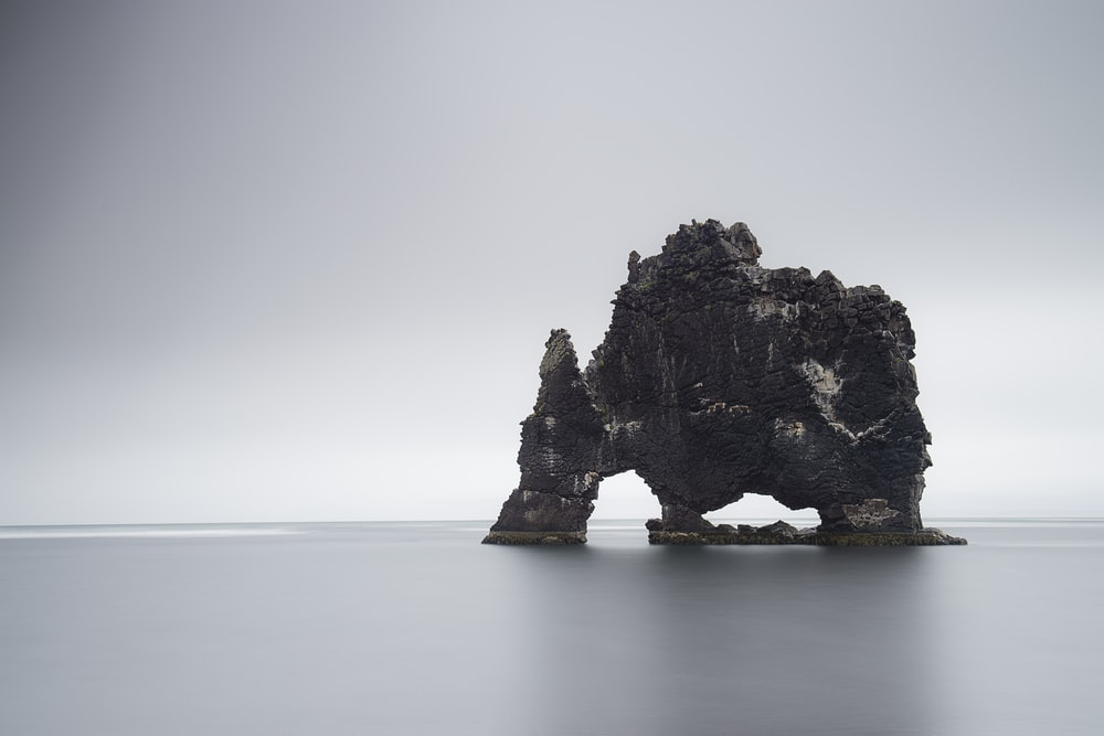black rock formation on body of water