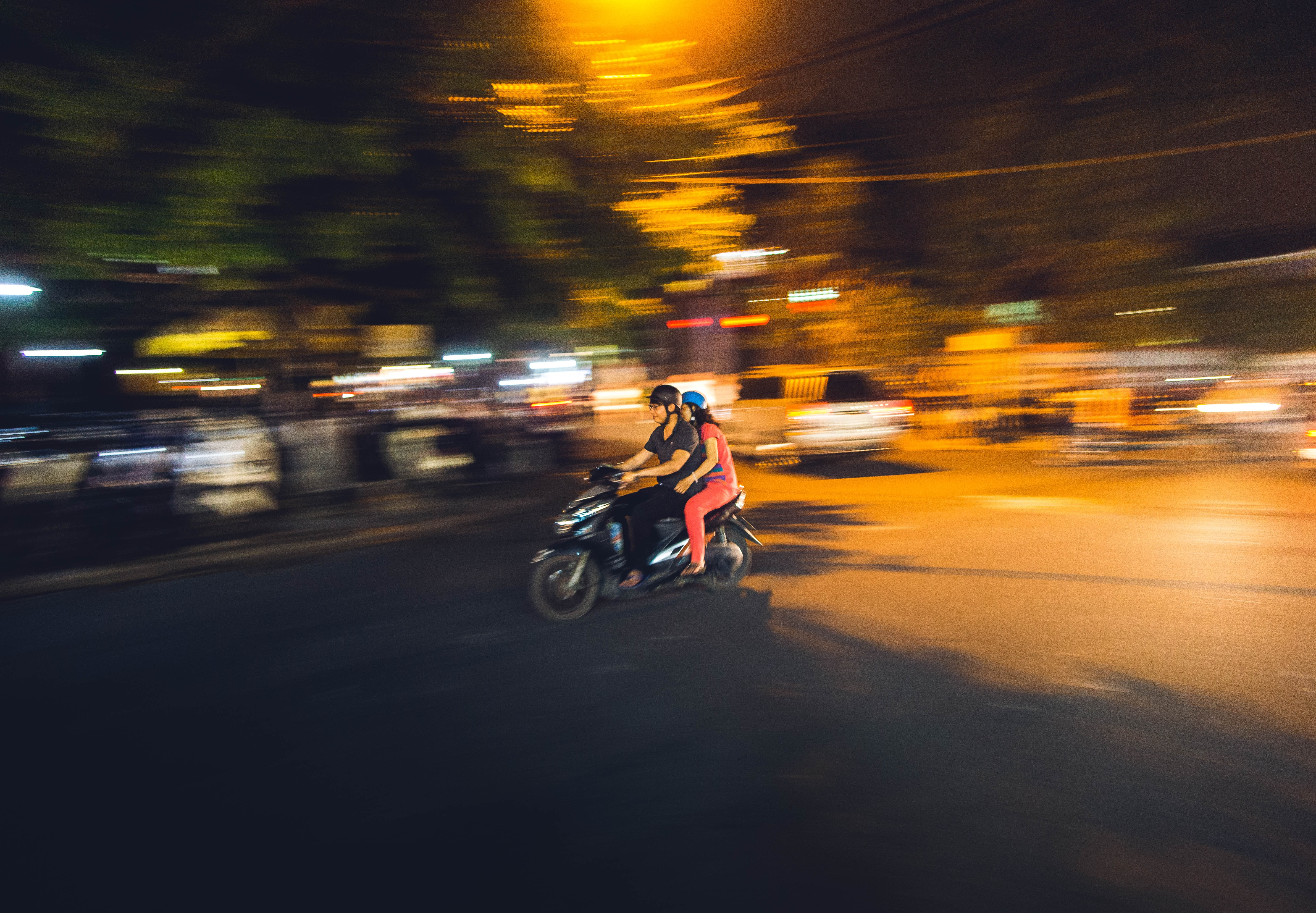 Two people riding motorbike at night under street lights in urban area