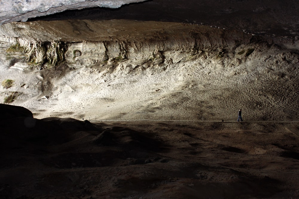 person walking inside cave with sun lights