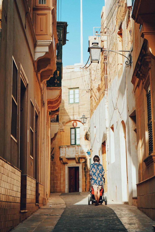 woman pushing stroller passing through alleyt
