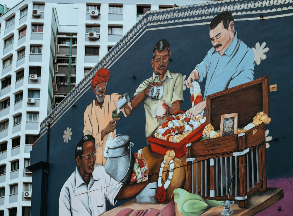four man eating and drinking wall painting near tall building at daytime