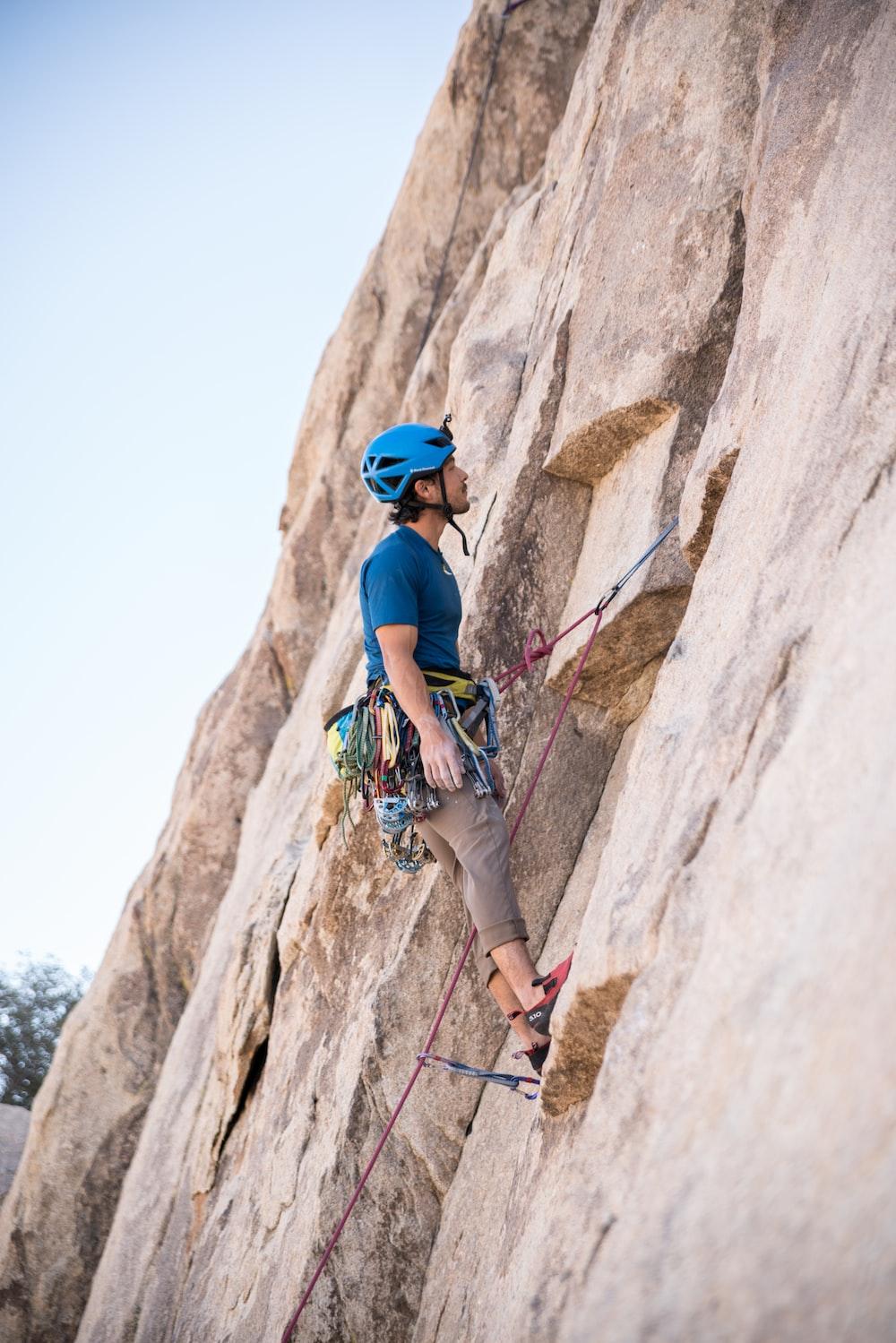 man doing rock climbing at daytime