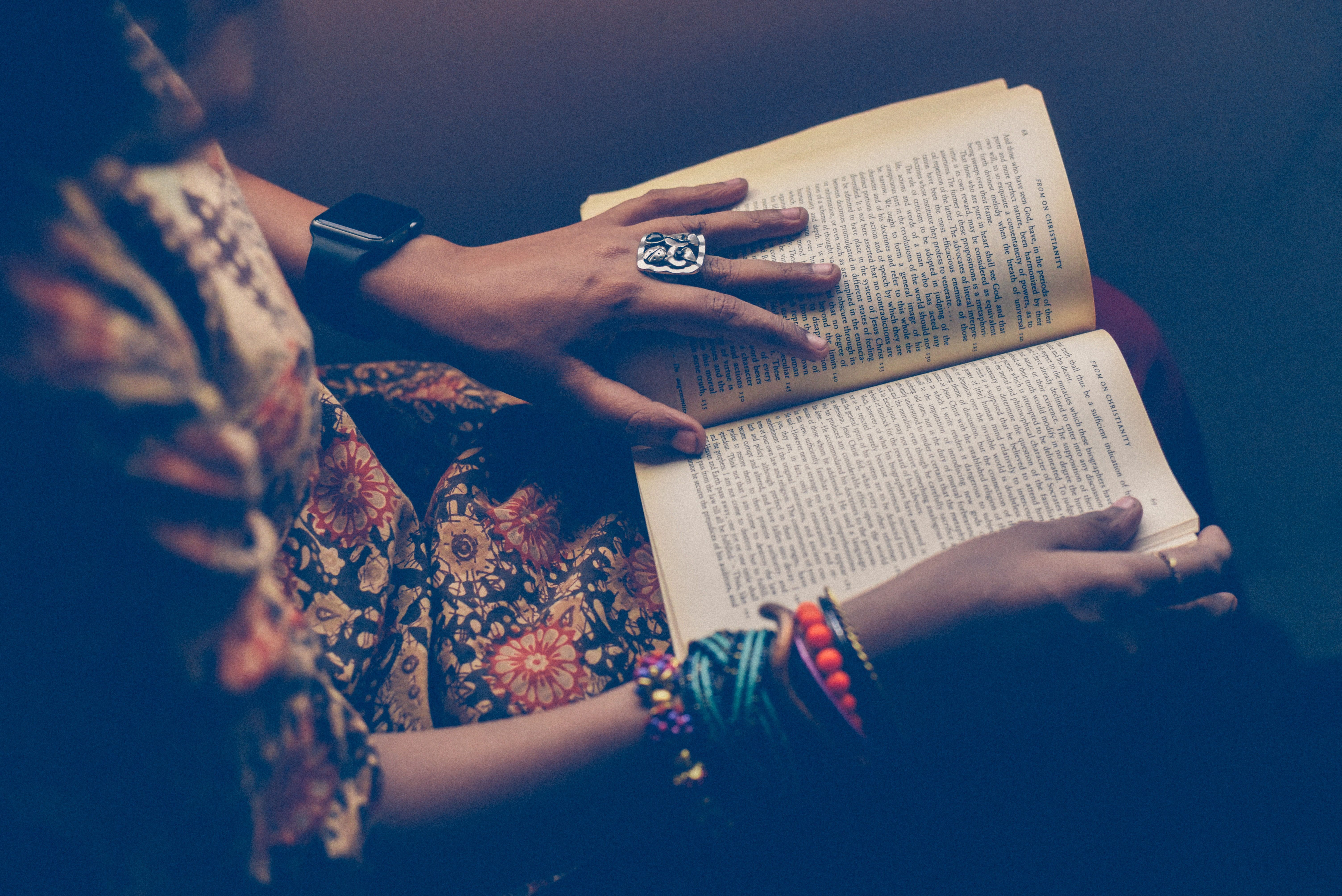 A woman with an Apple Watch and colorful bracelets on her wrists reading a book