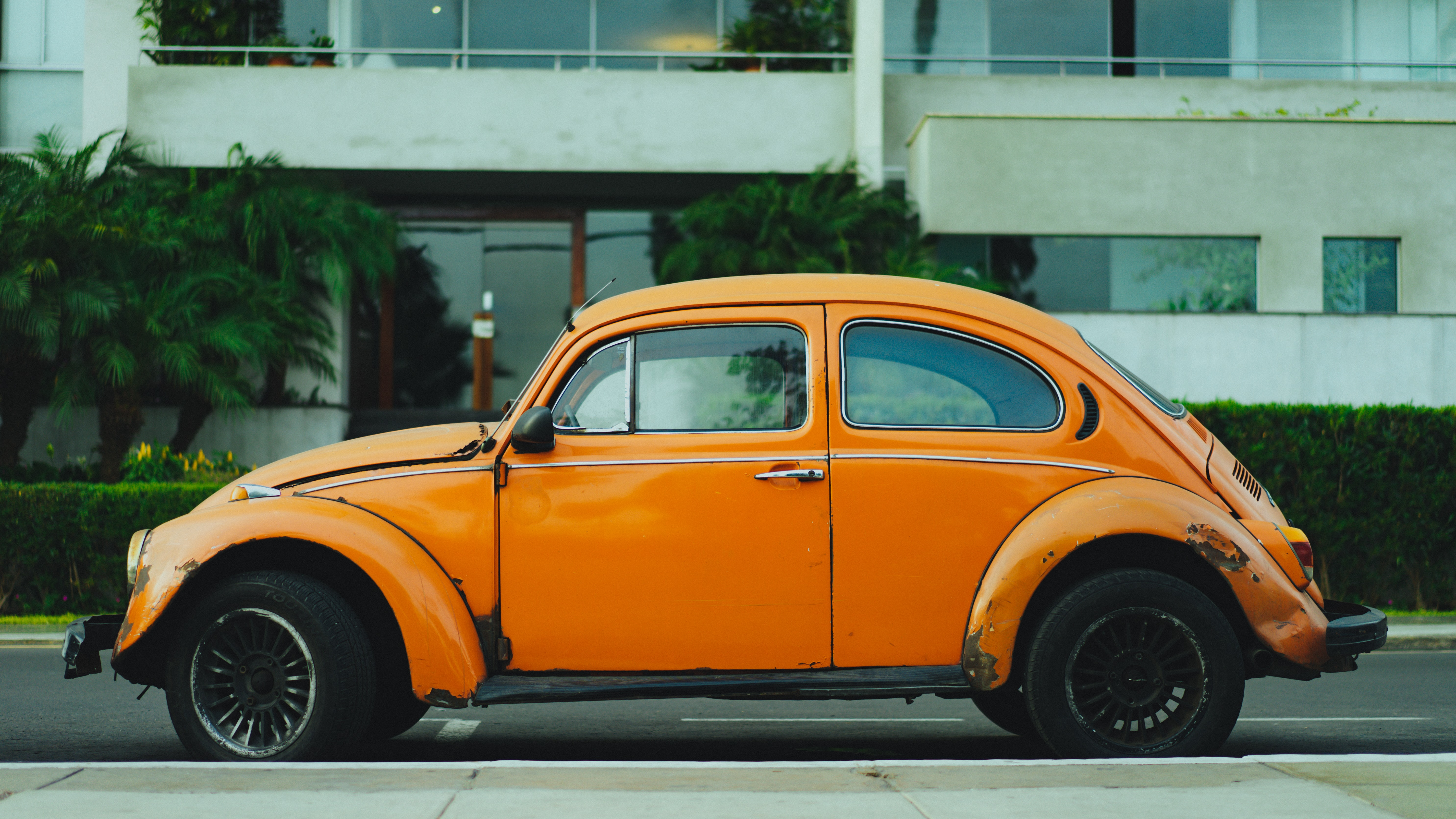 Rusted old vintage orange Volkswagen beetle parked in front of apartment complex