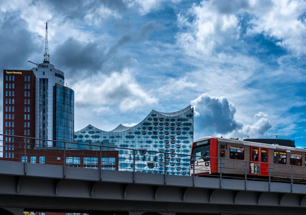 train running on rail near buildings during daytime