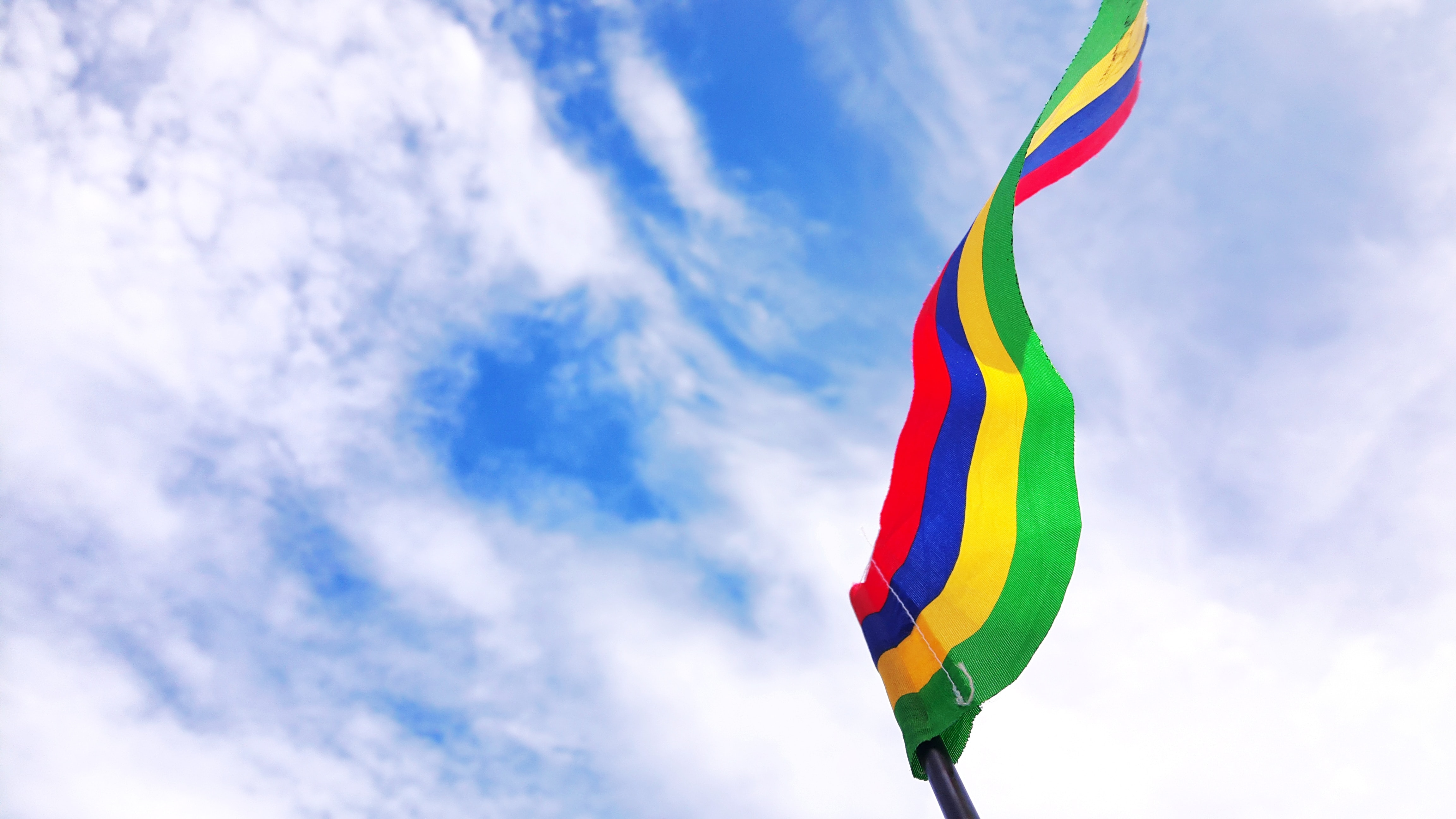 red, blue, yellow, and green striped flag under blue sky