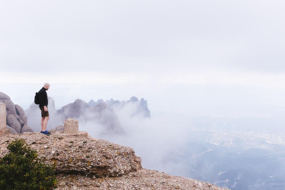 man standing white facing cliff