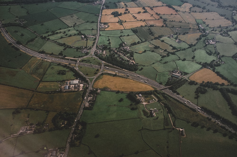 aerial photography of concrete roadway and green field