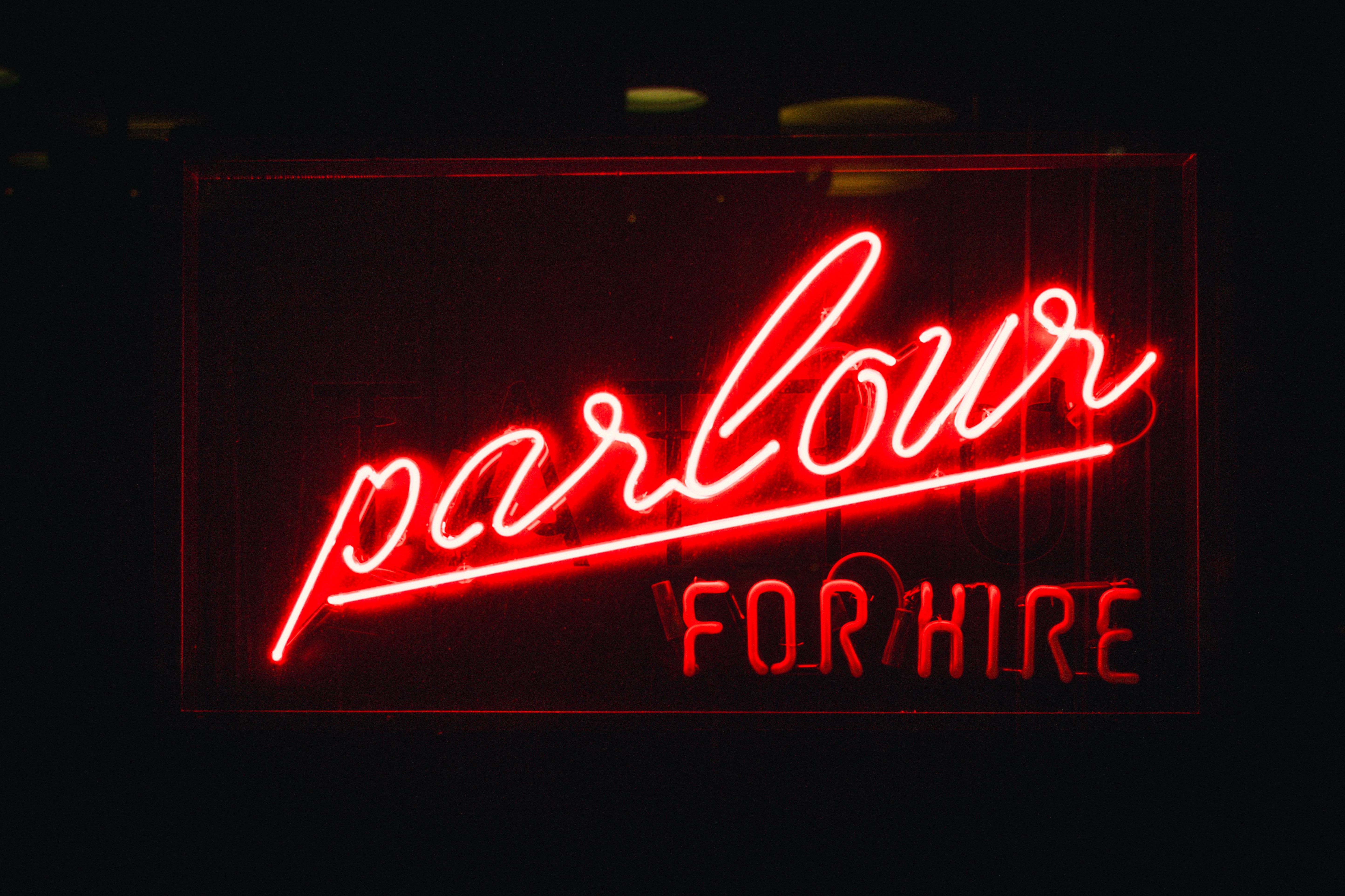 "Red neon ""parlour for hire"" sign in the dark"