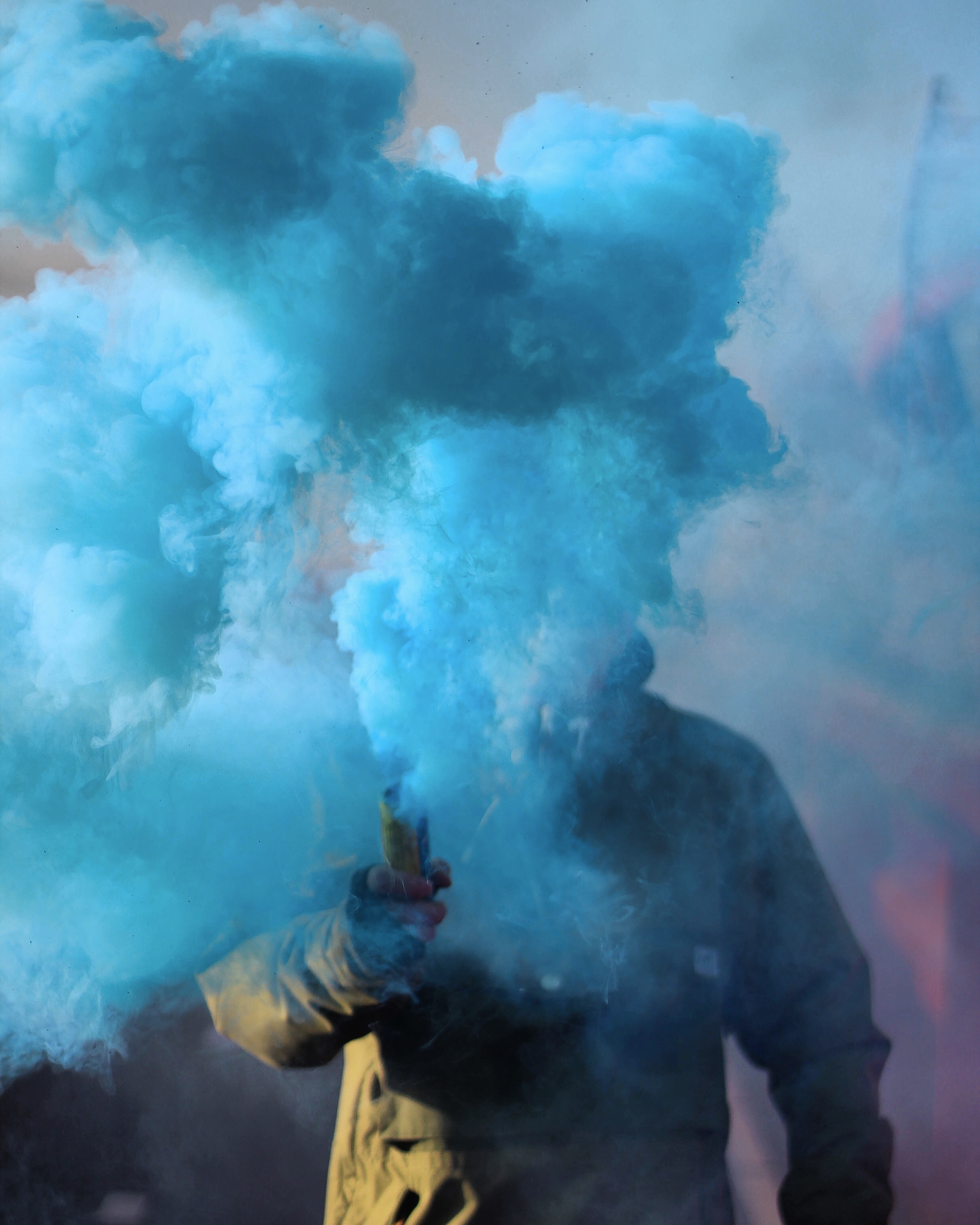 person holding stick with blue smoke
