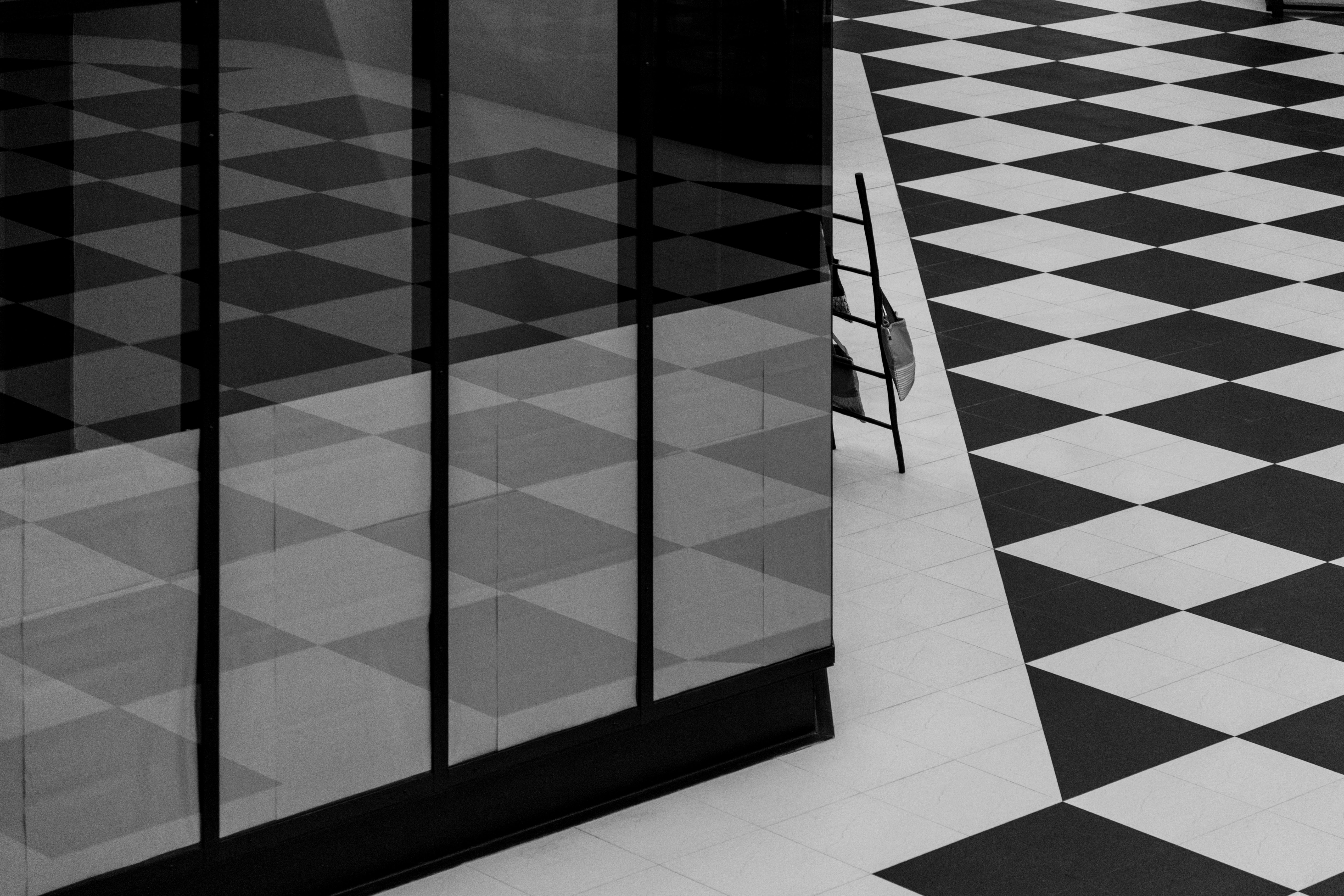 Black and white shot of monochrome square floor pattern and tall window with reflection