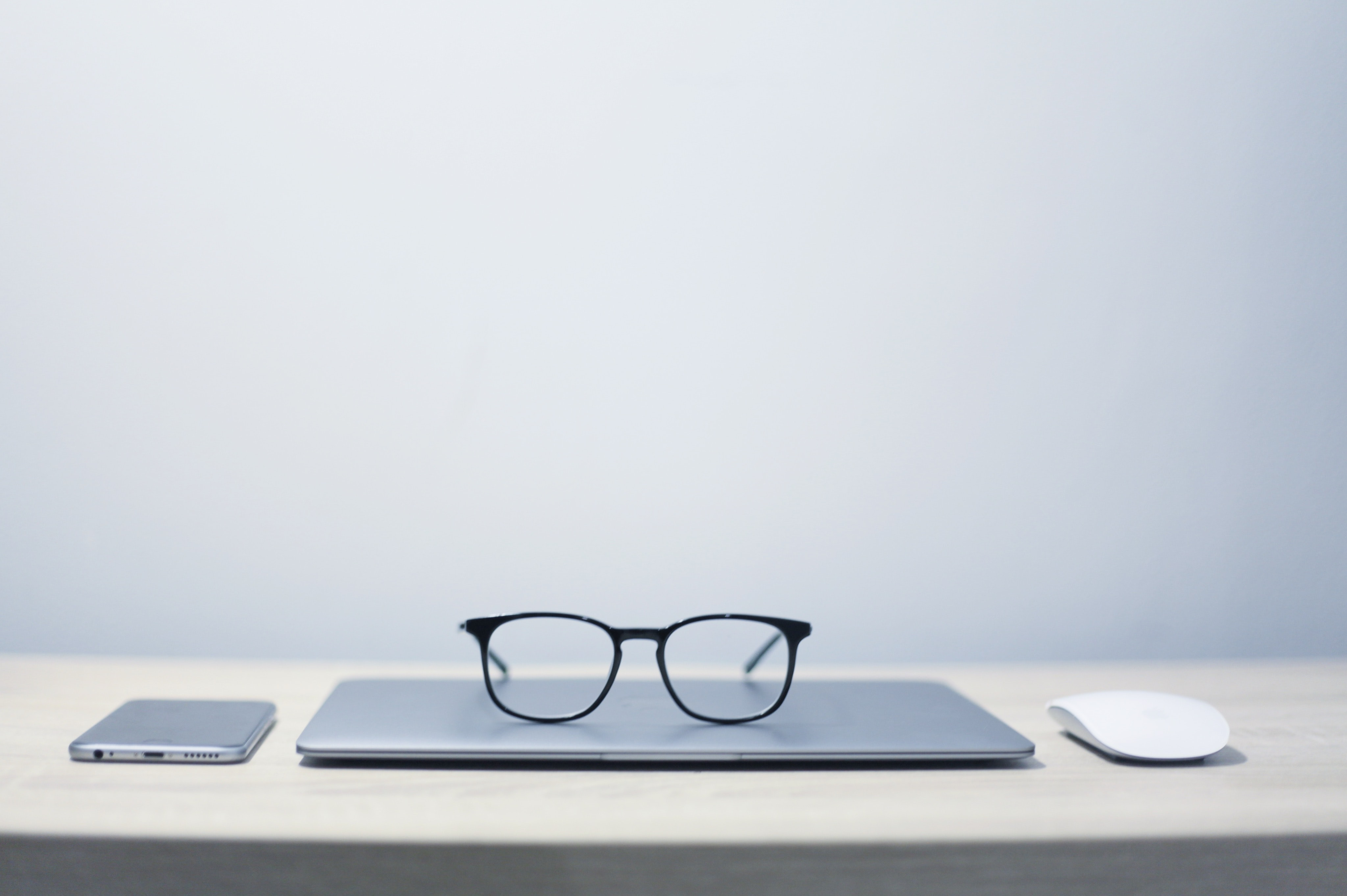 A pair of glasses on top of a laptop with a phone on one side and a mouse on the other