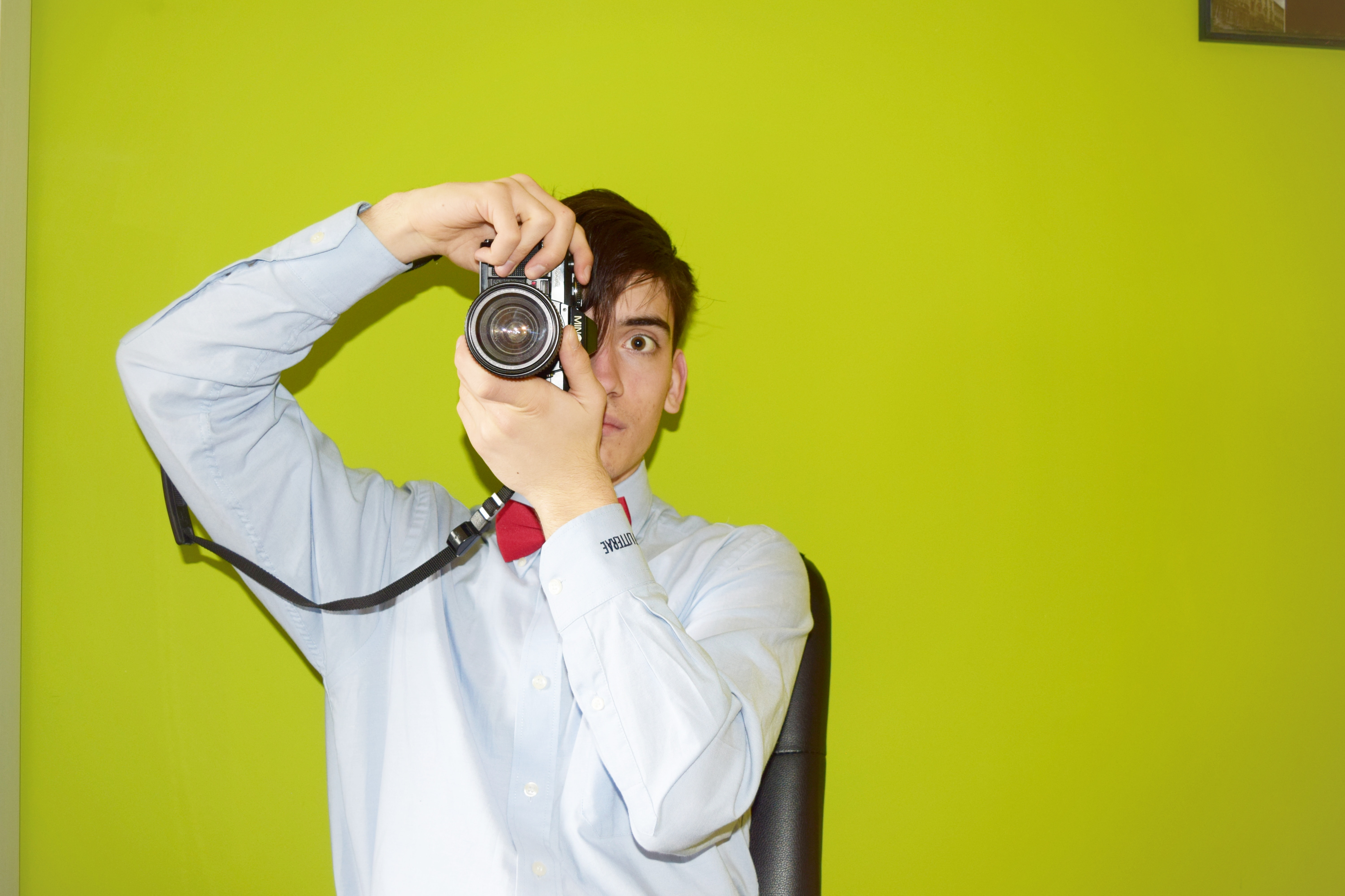 A person faces forward holding a camera against a bright green wall
