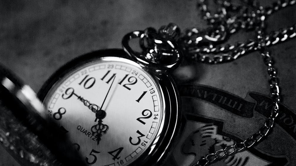 grayscale photography of analog pocket watch