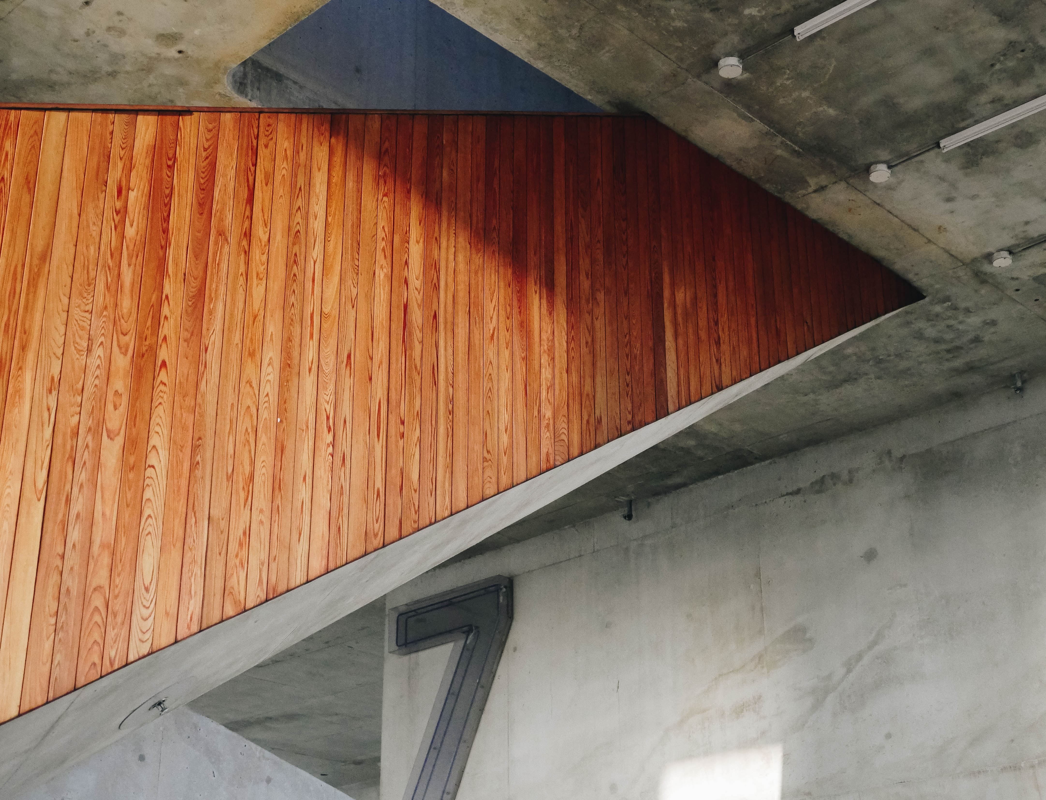 Wooden panelling on the side of a staircase in a building with bare concrete walls