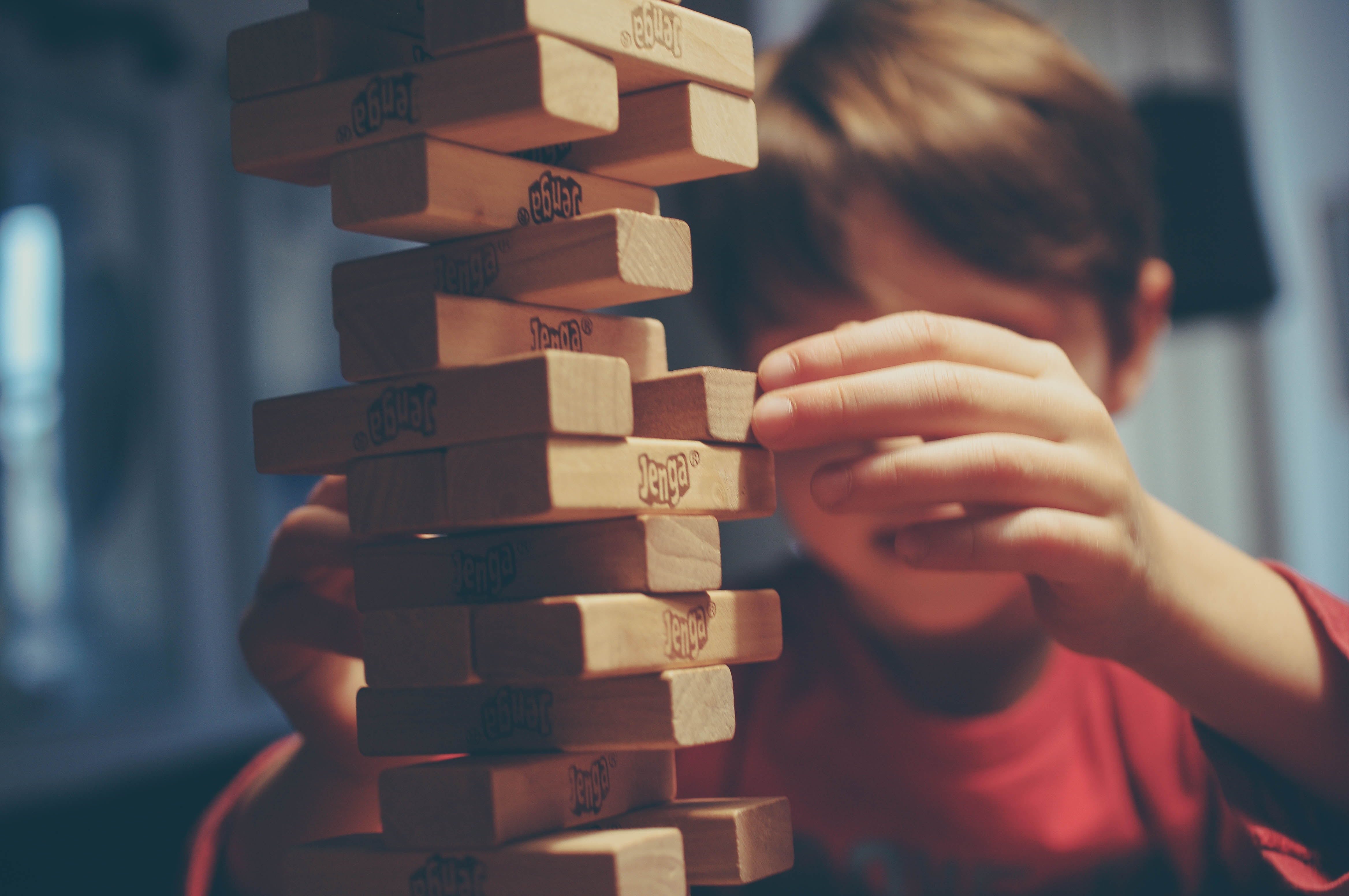A child playing with a Jenga block tower