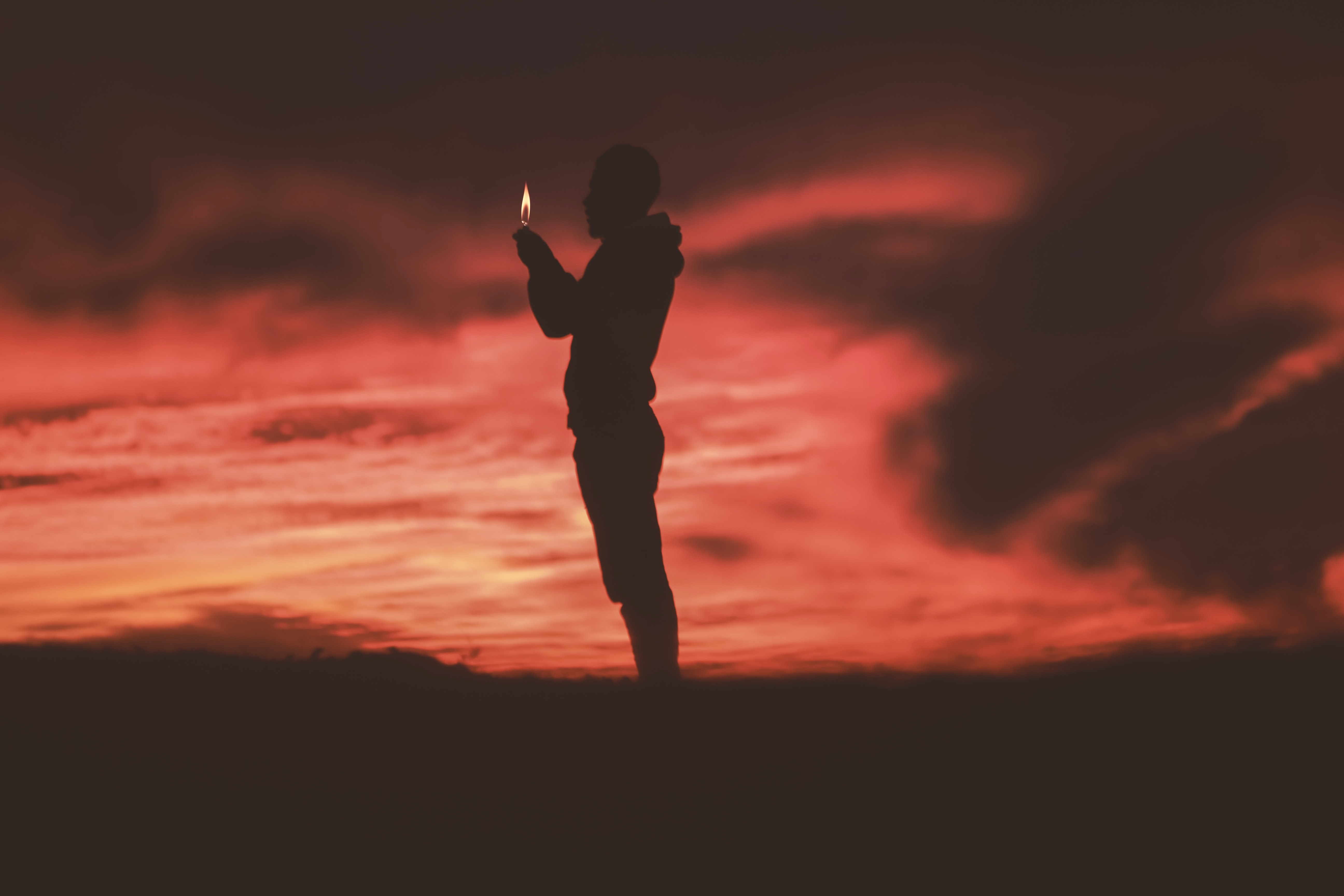 A silhouette of a man holding a lighter against a red sky at dusk