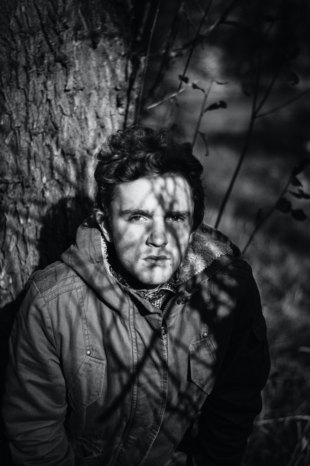grayscale photo of man under tree