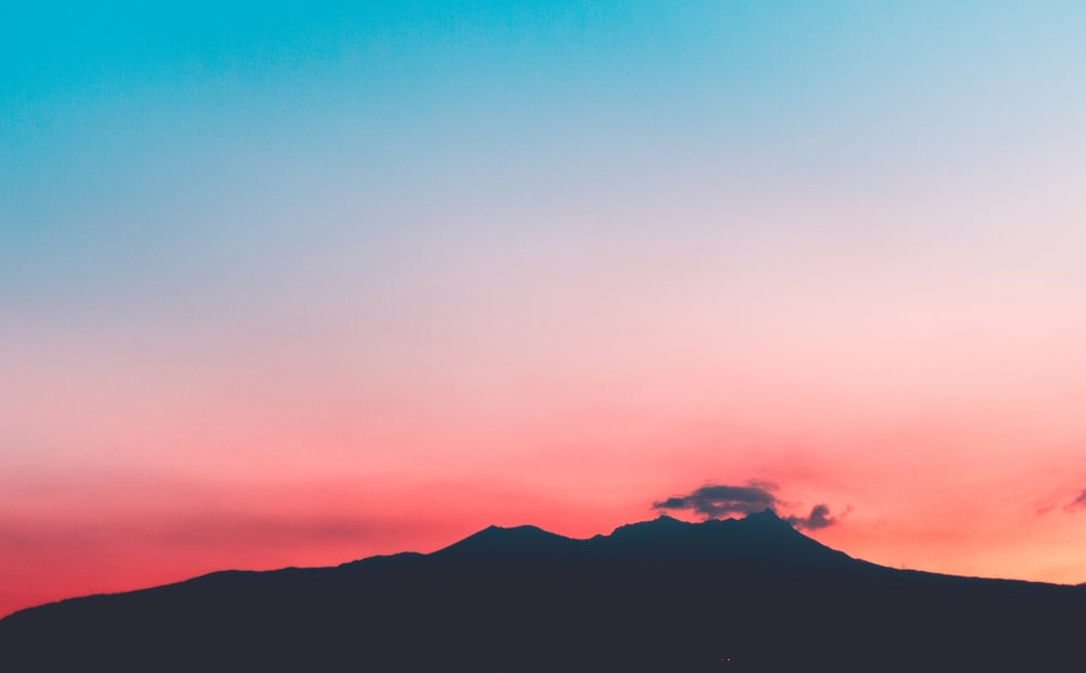 silhouette of mountain under pink and blue skies