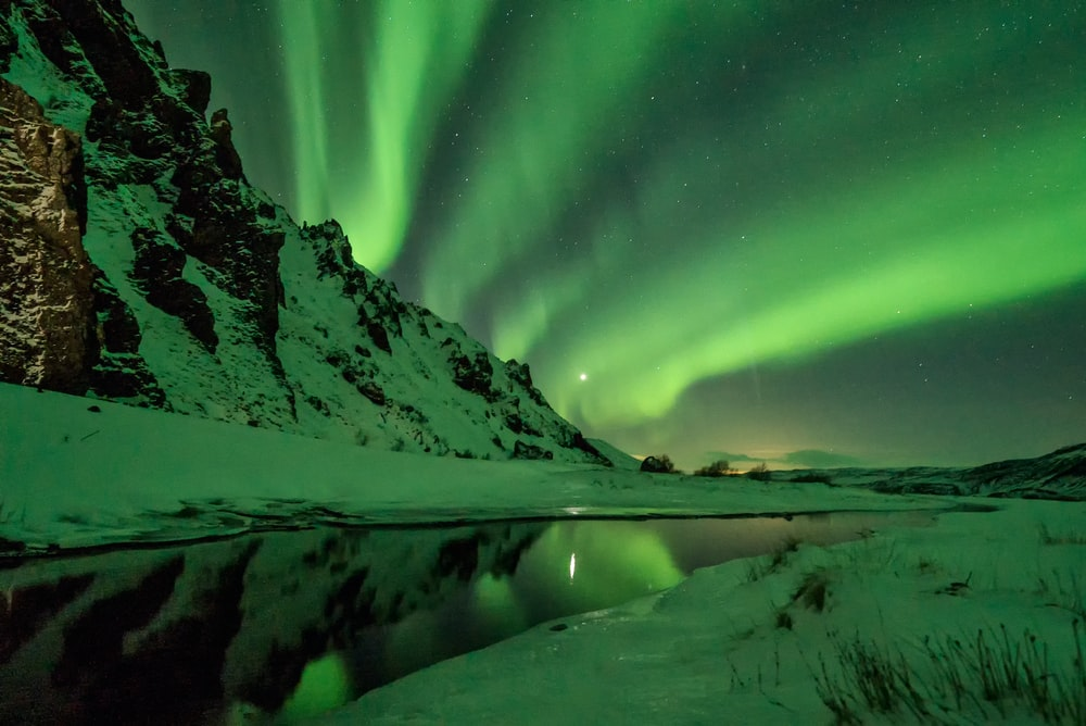 snow covered mountain with aurora borealis