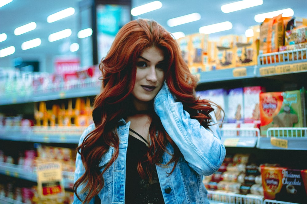 woman in blue denim jacket holding her face in convenient store
