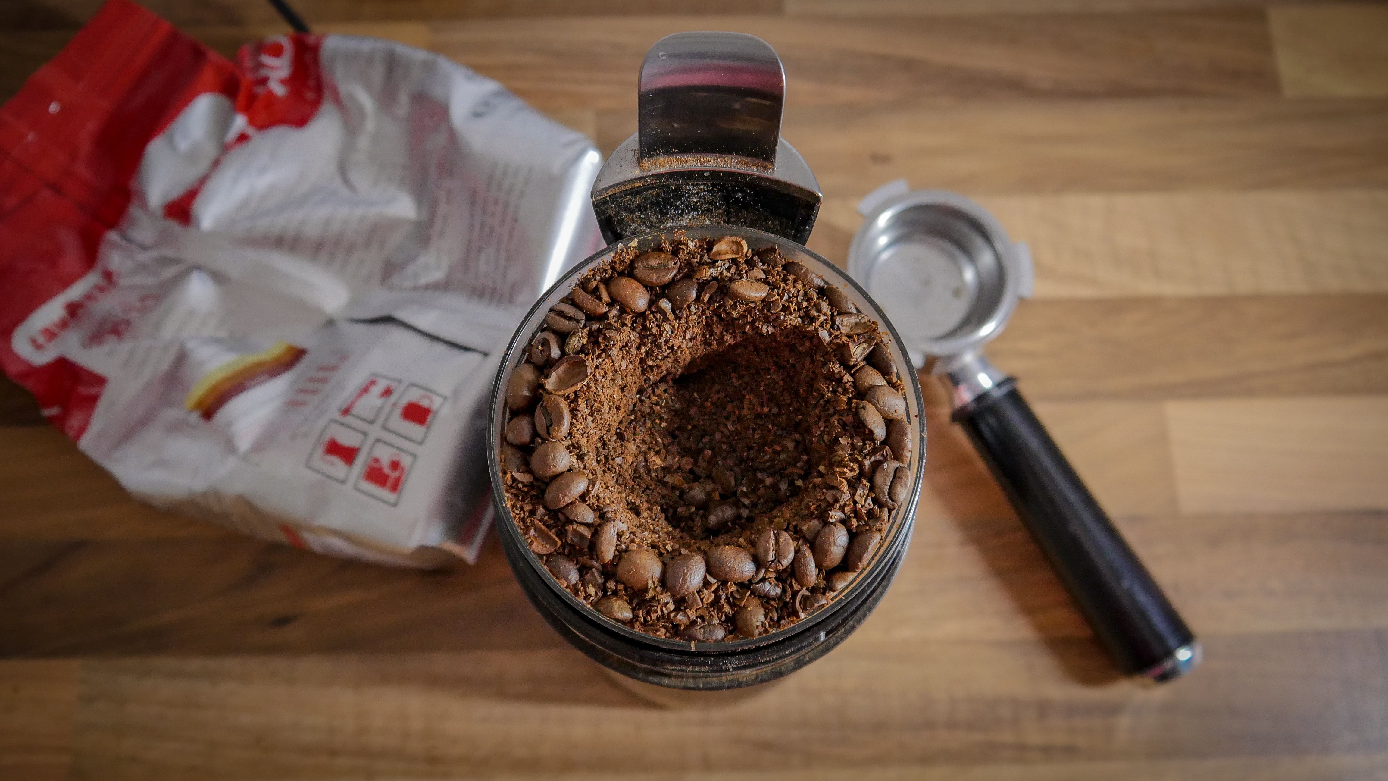 Coffee grinder full of beans and grounds