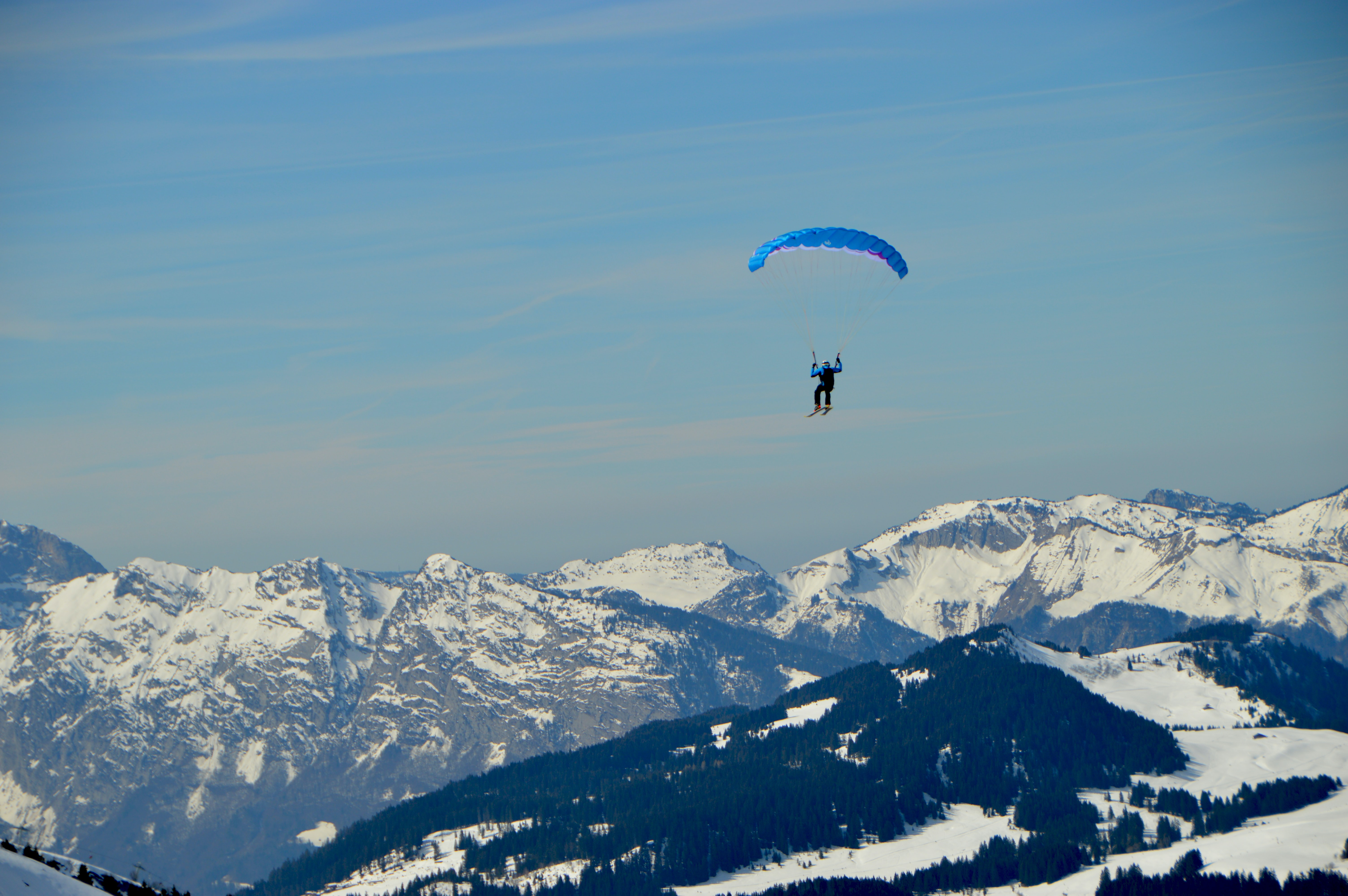 Person parachutes over mountains in a blue landscape