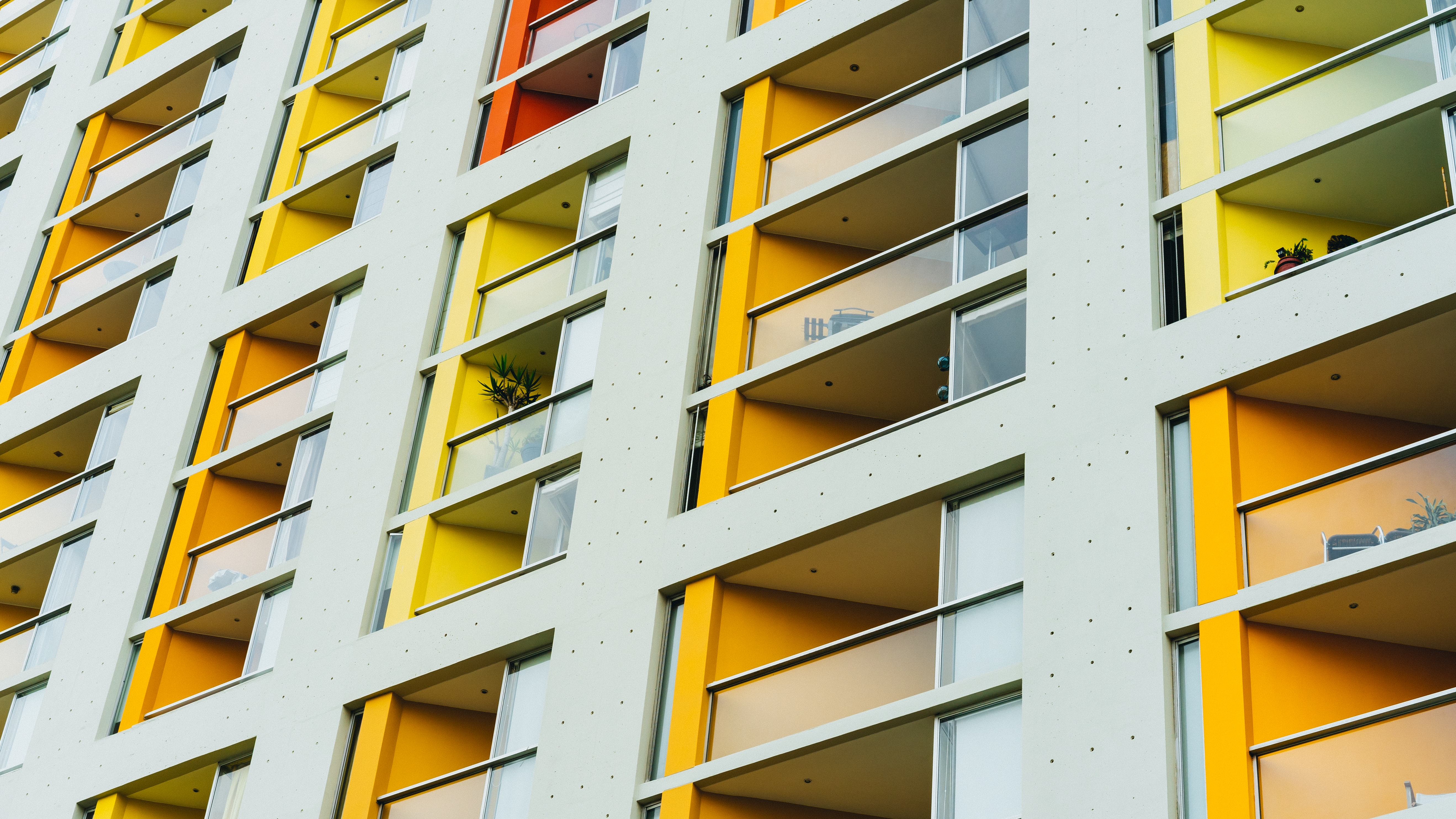 Balconies with their walls painted in various colors in an apartment block