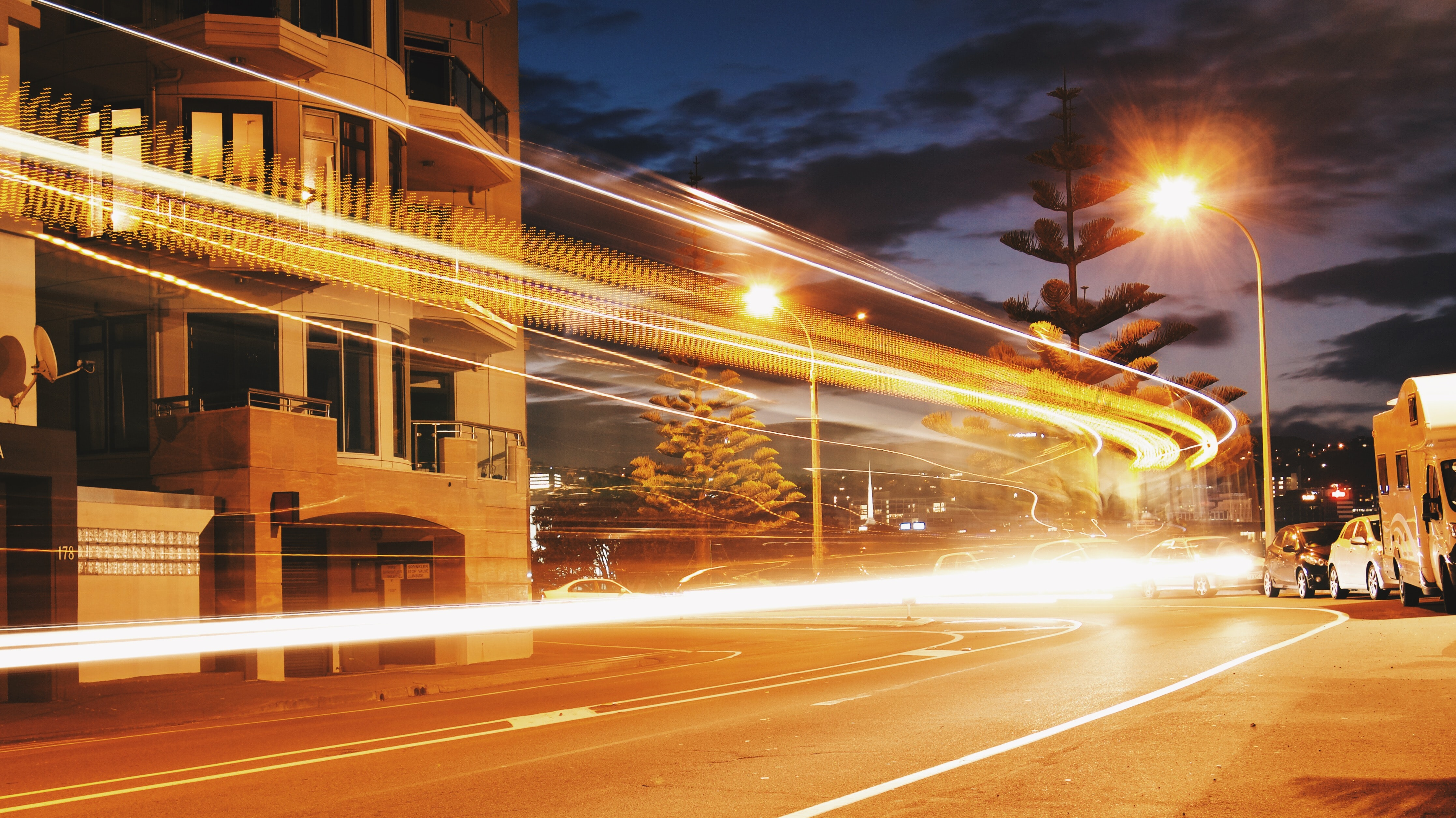 A vivid and bright shot of street lights, with light trails from a traffic timelapse
