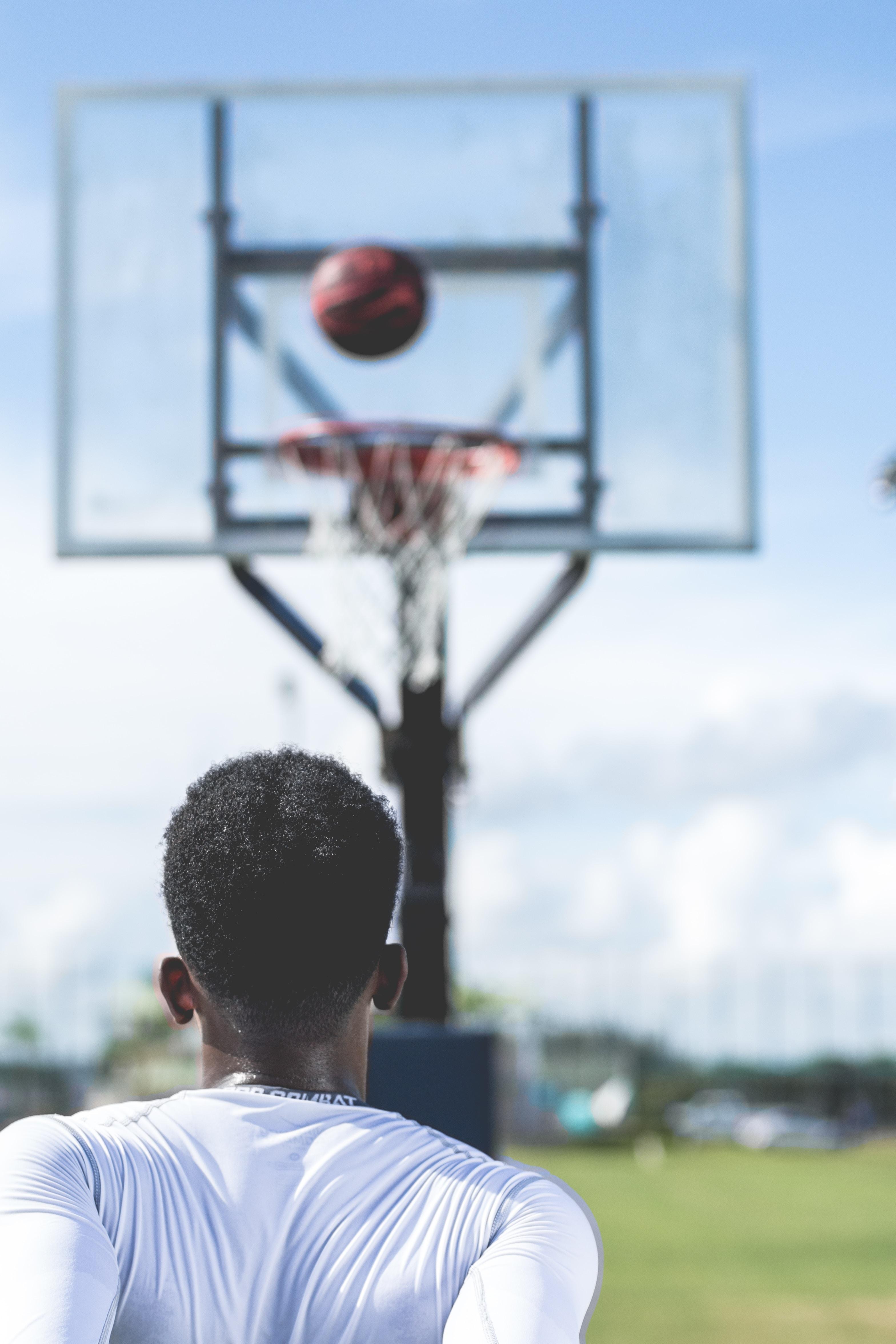 man shoot the ball on basketball ring