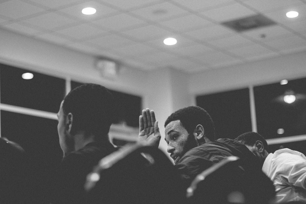 grayscale photography of man raising his hand