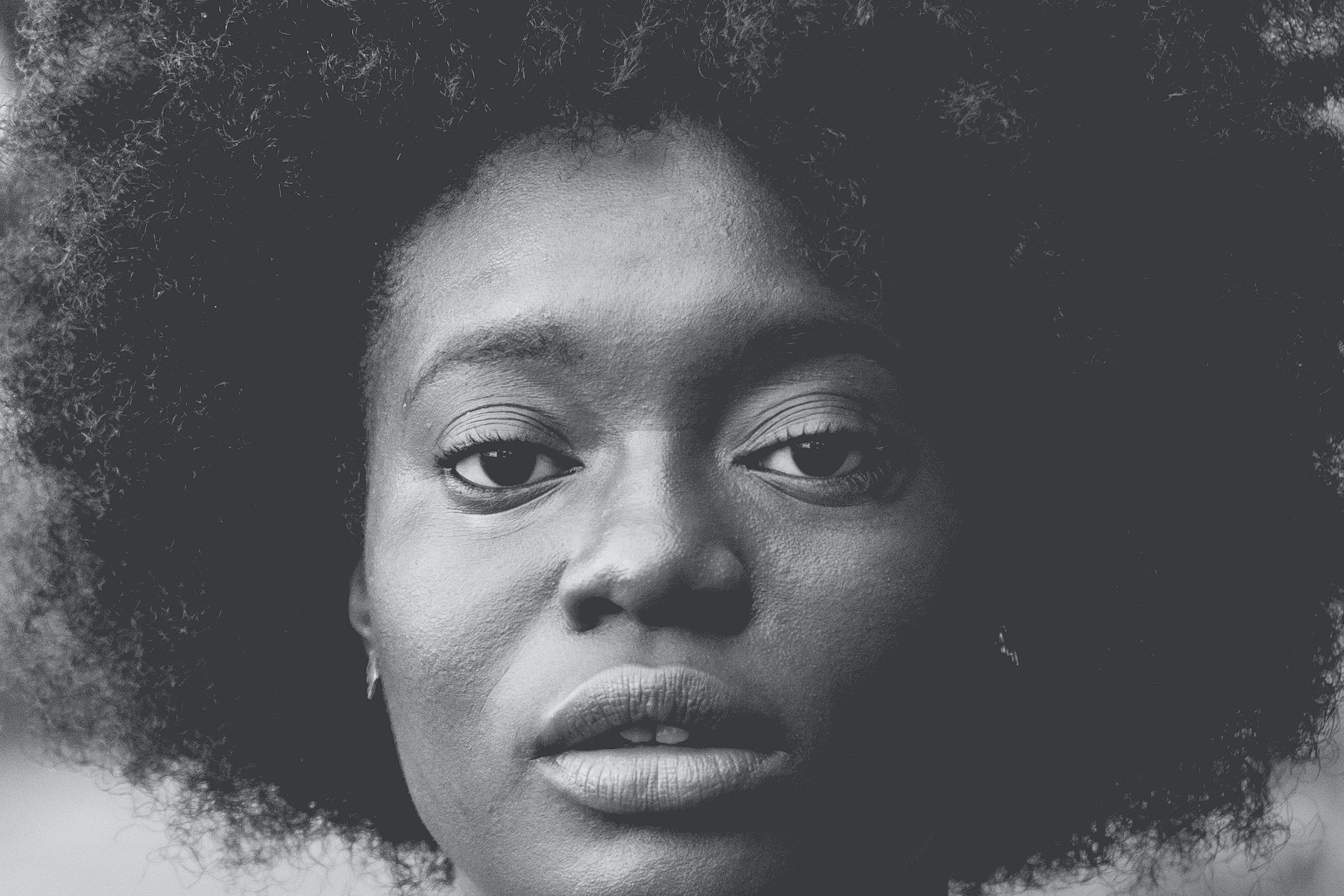 Black and white close up shot of attractive woman with afro hair