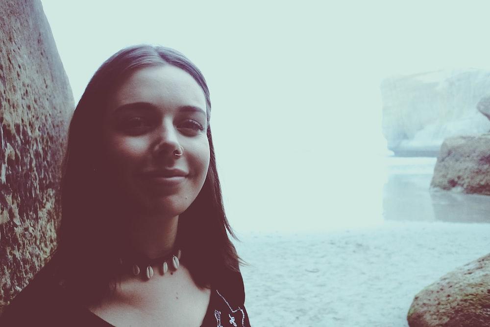 woman taking selfie near body of water and rocks