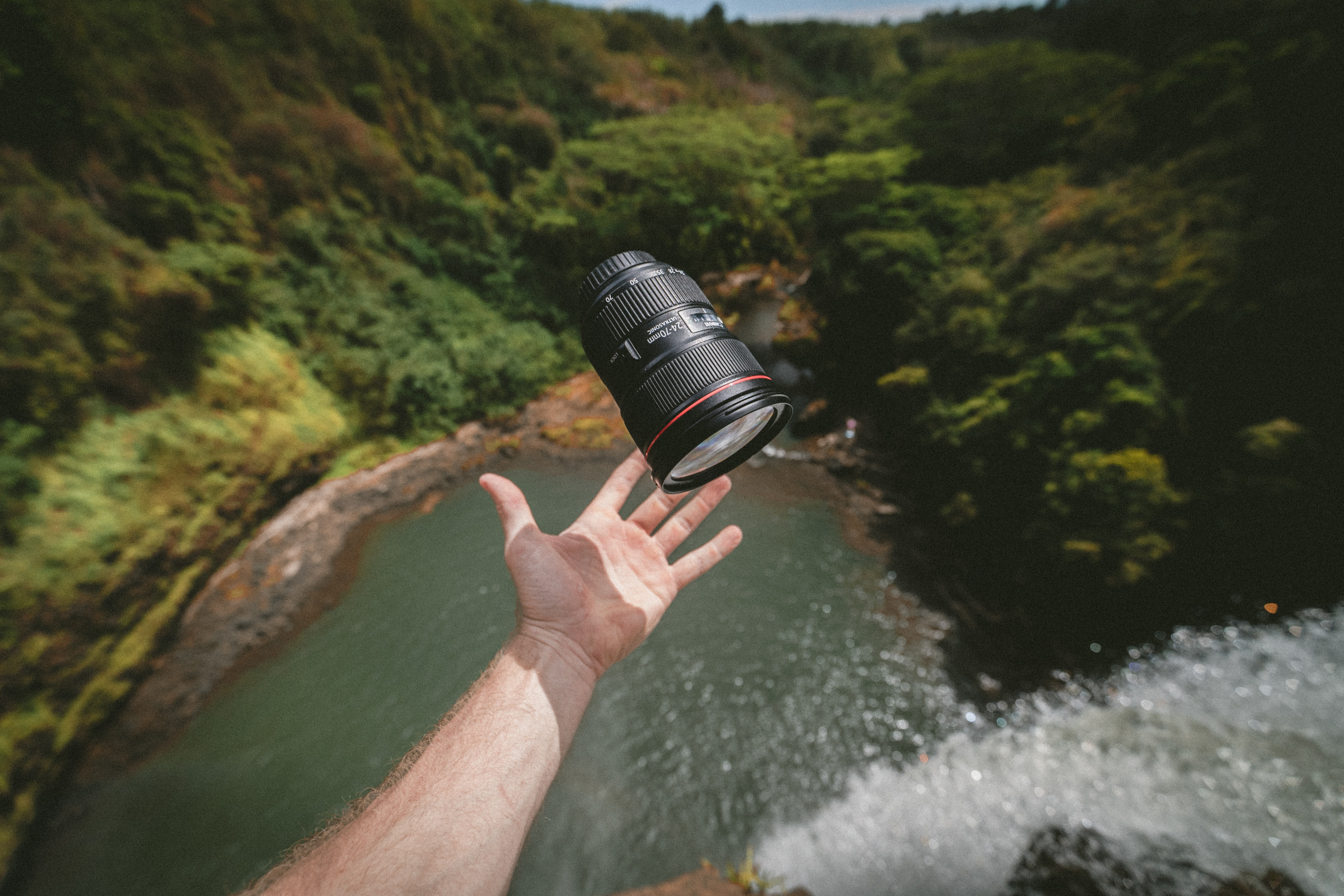 A man throwing a zoom lens up in the air over a tall waterfall
